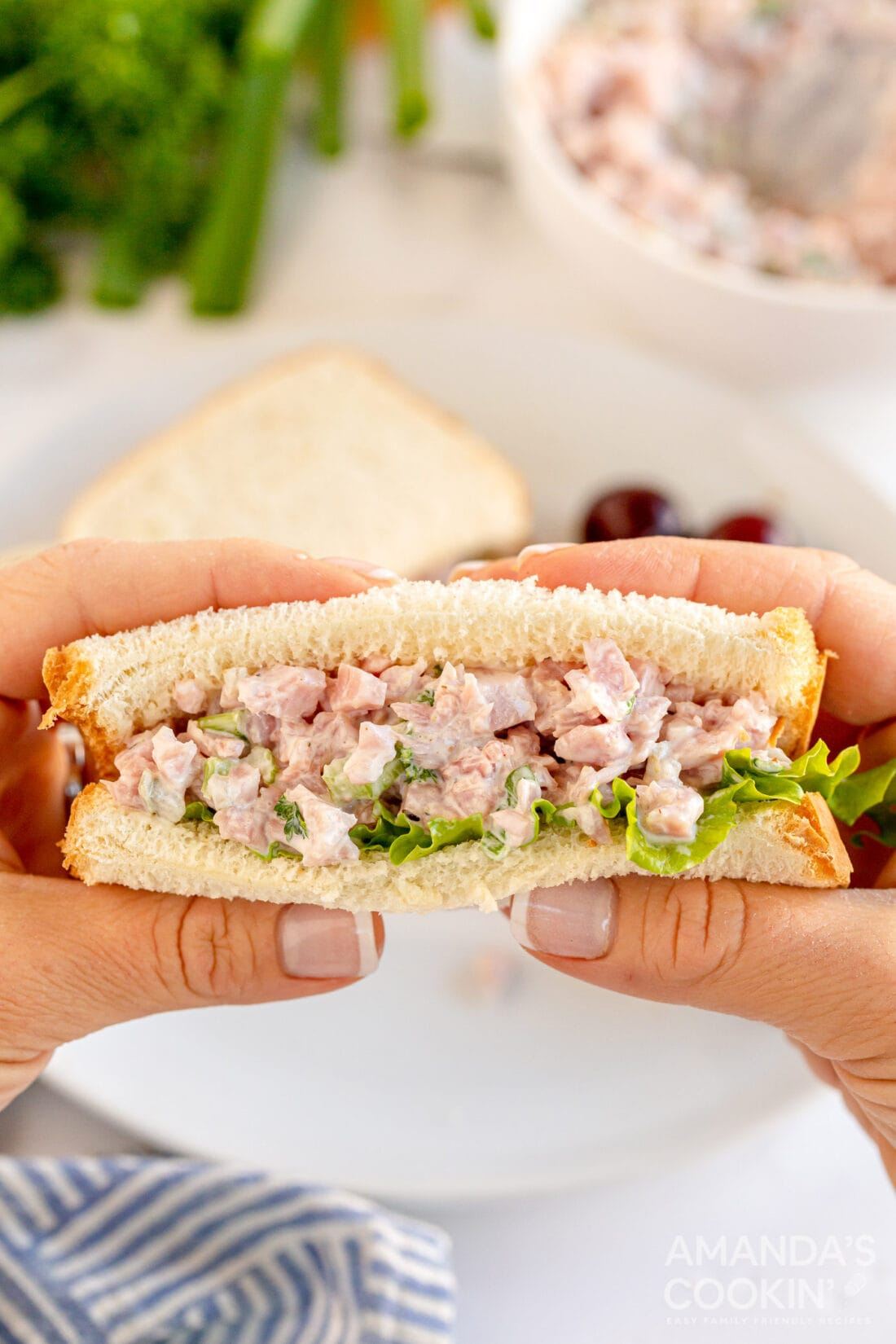 woman holding ham salad sandwich