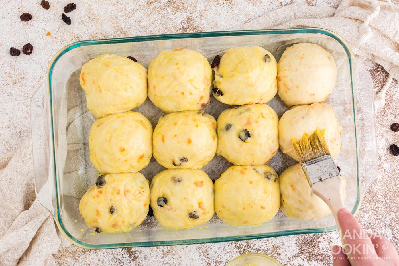 brushing tops of dough balls with eggwash