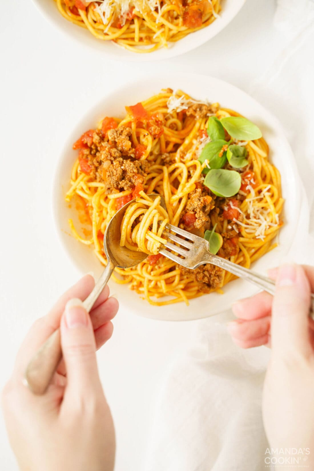 turning fork on spoon to pick up spaghetti noodles