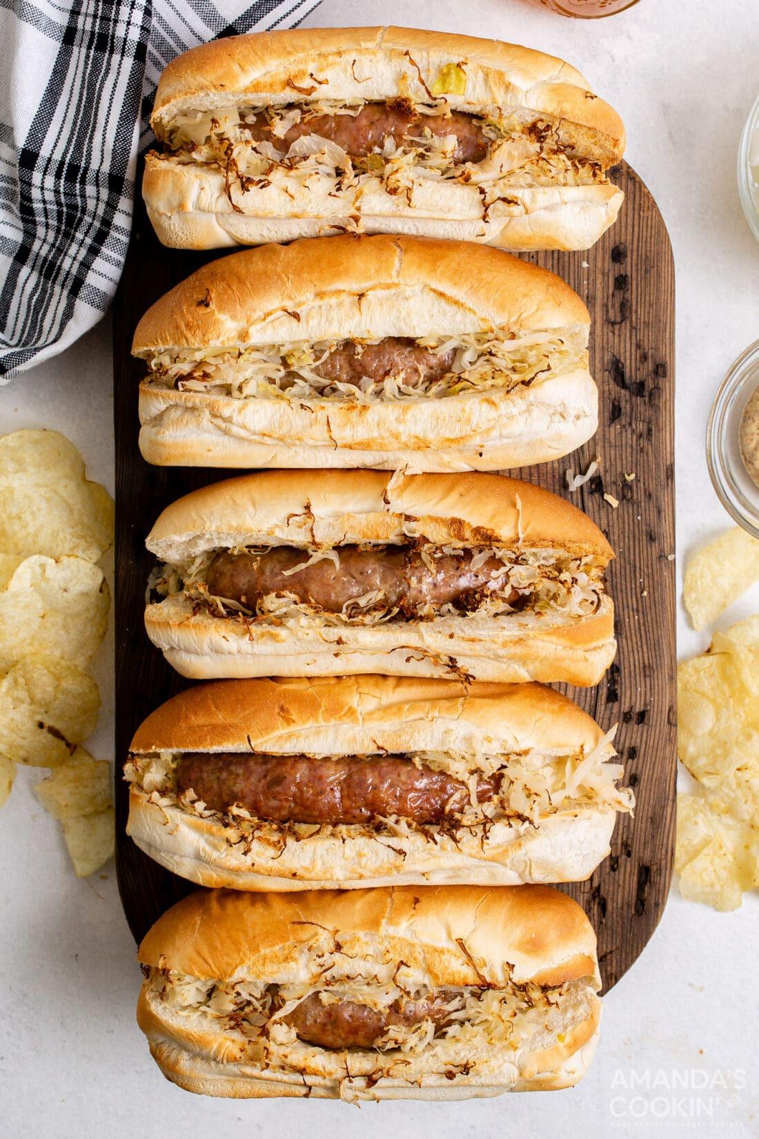 air fryer bratwurst in buns with sauerkraut on cutting board