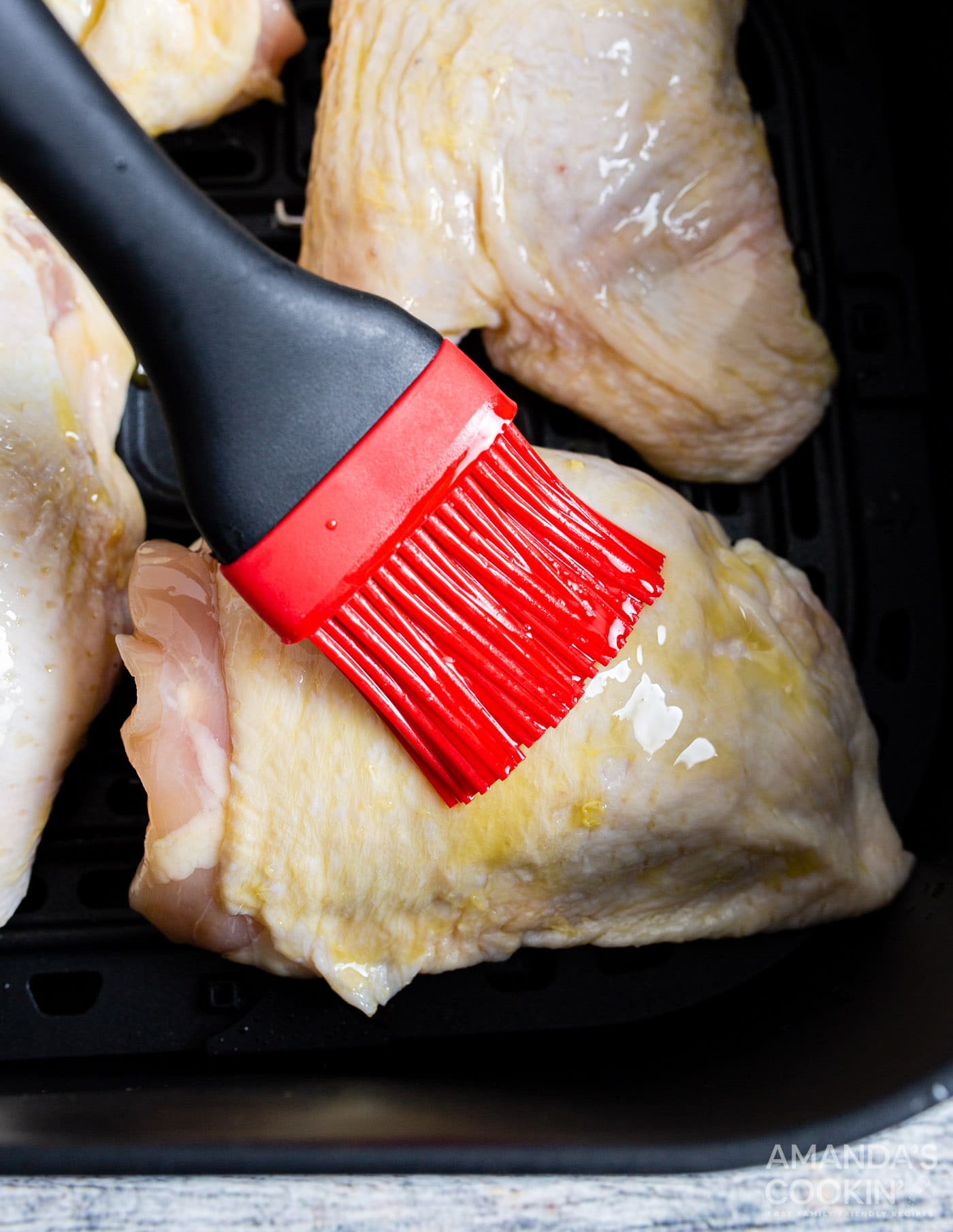 brushing chicken thighs with oil