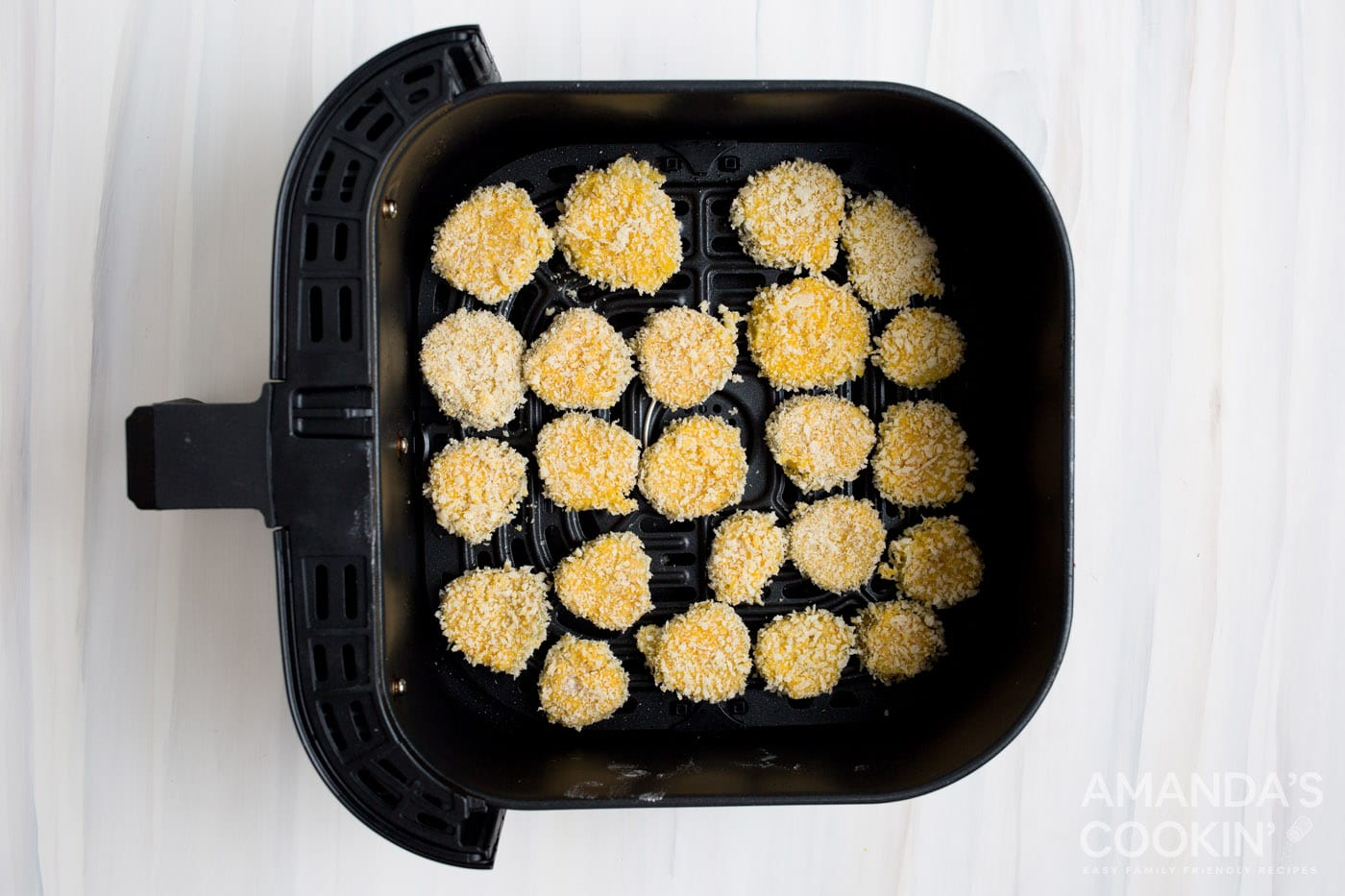 panko coated pickle chips in an air fryer basket