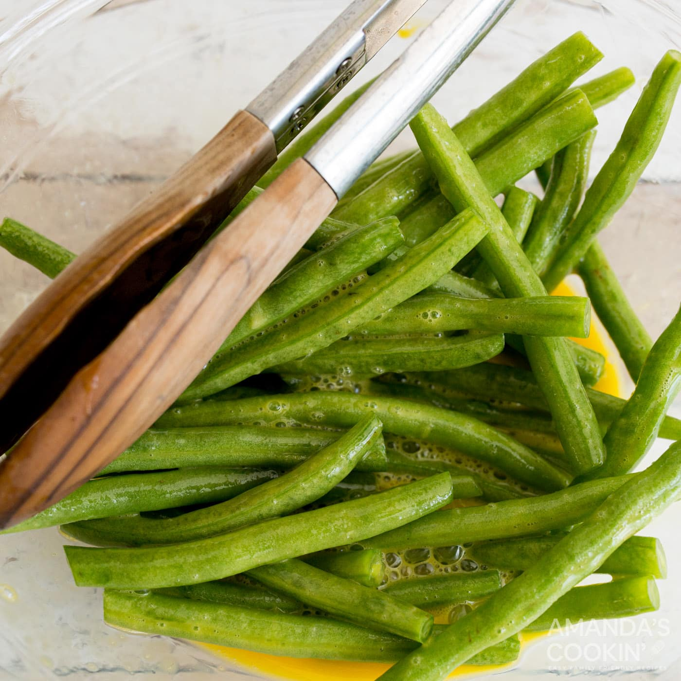 tossing green beans in a bowl of eggs