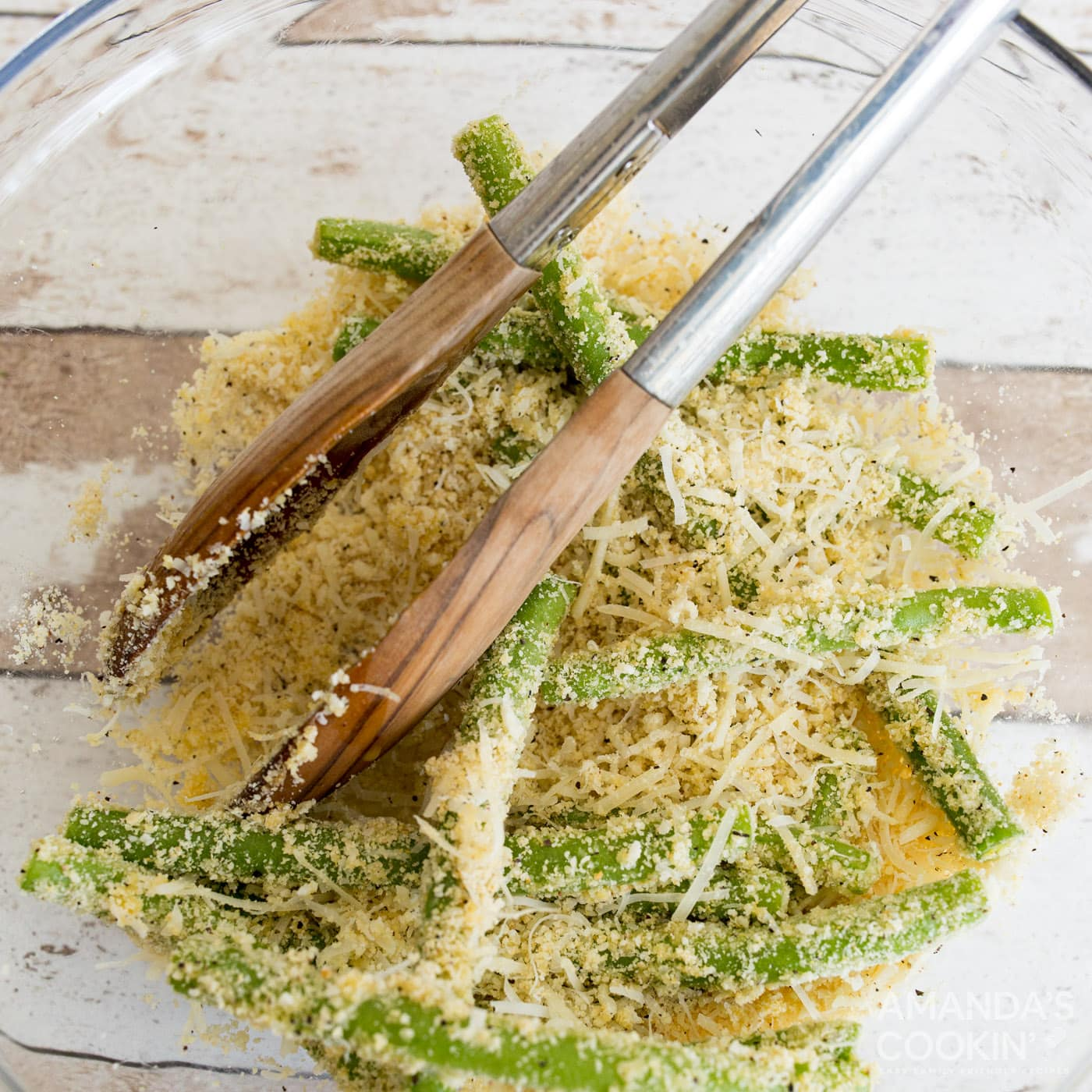 tossing green beans with almond flour, parmesan, egg, and seasonings
