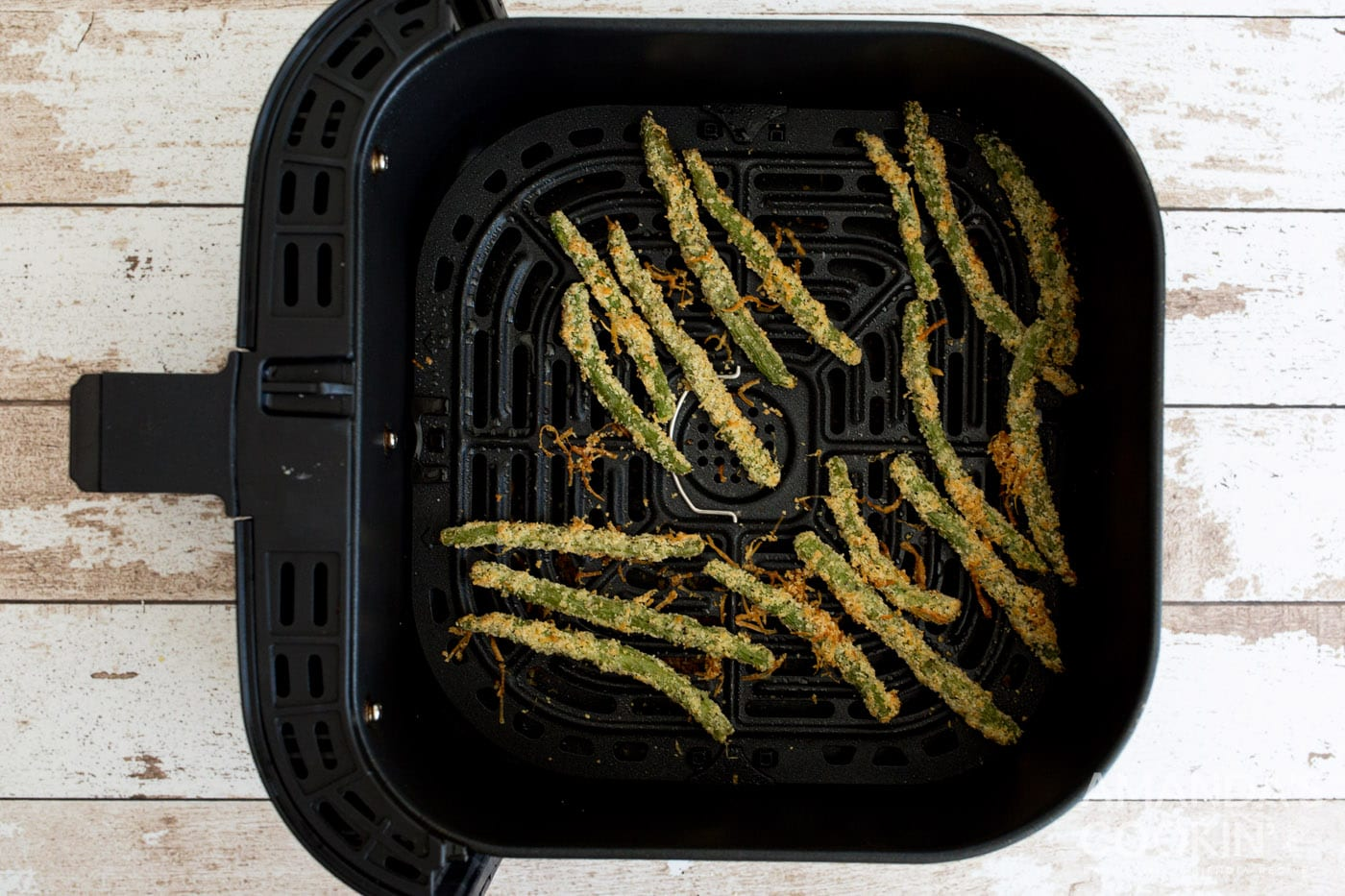 cooked green bean fries in air fryer basket