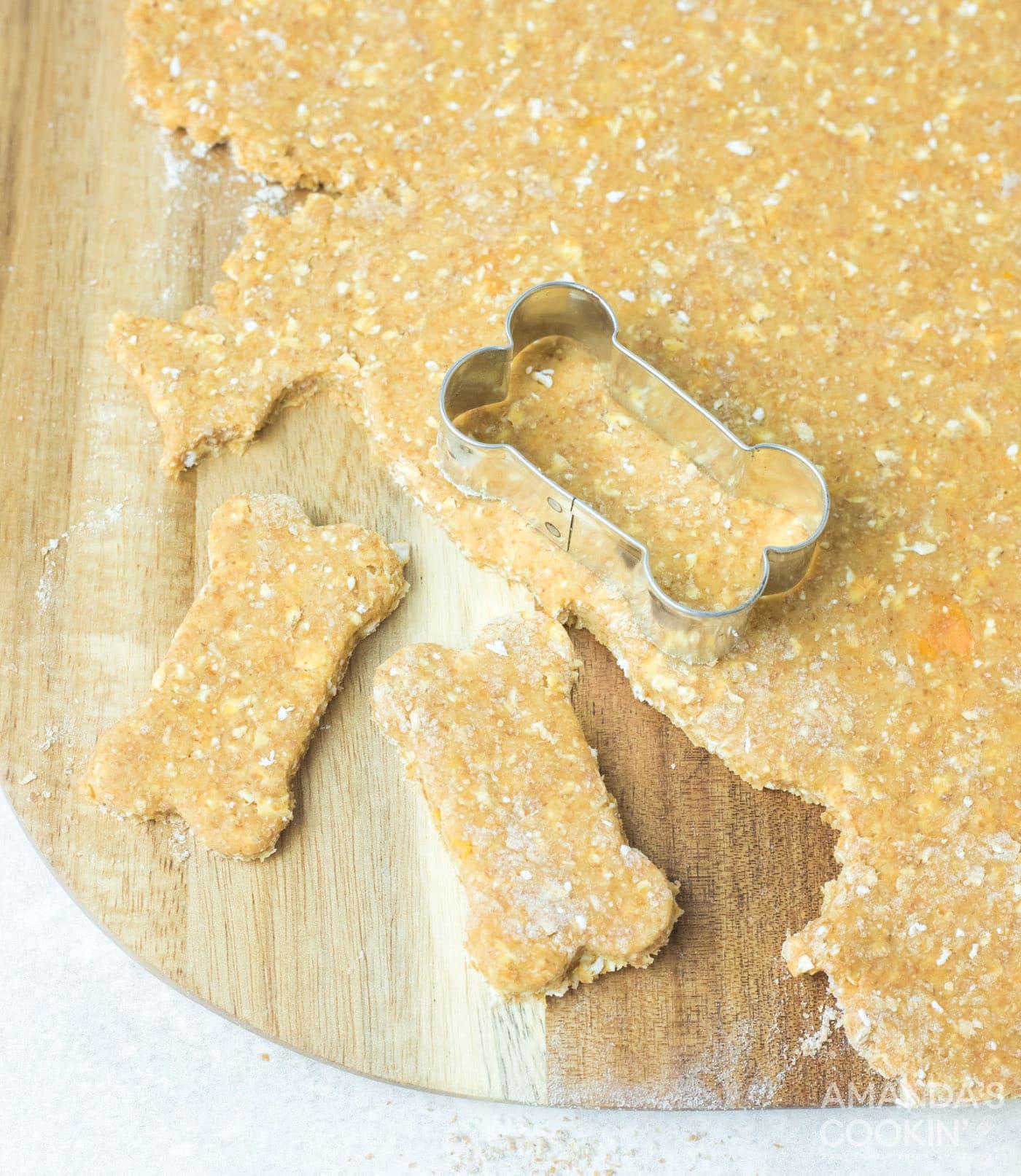 bone shaped cookie cutter cutting dough