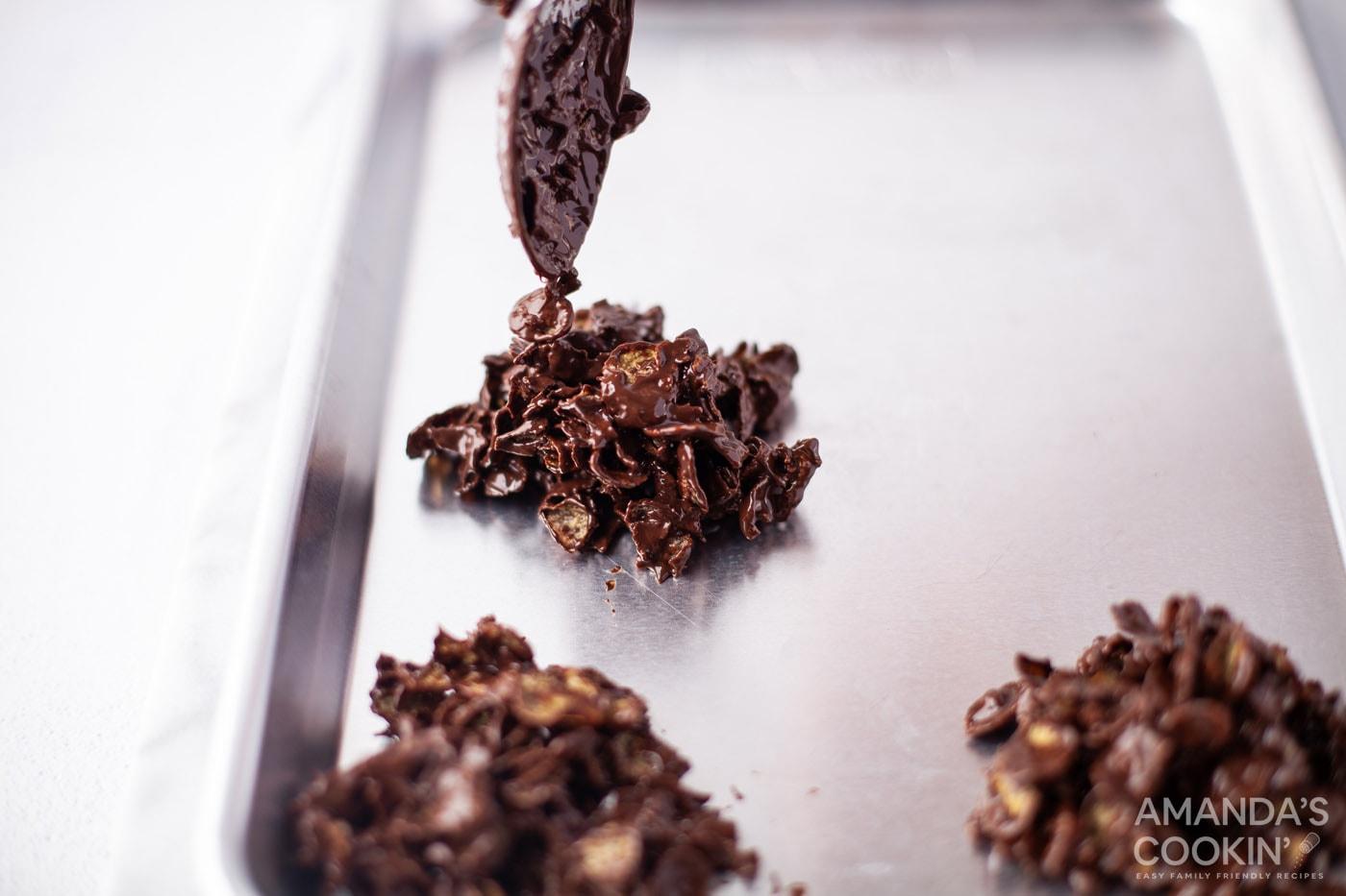 spooning dark chocolate cornflake cookies onto baking sheet