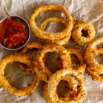 Air Fryer Onion Rings on parchment with dish of ketchup