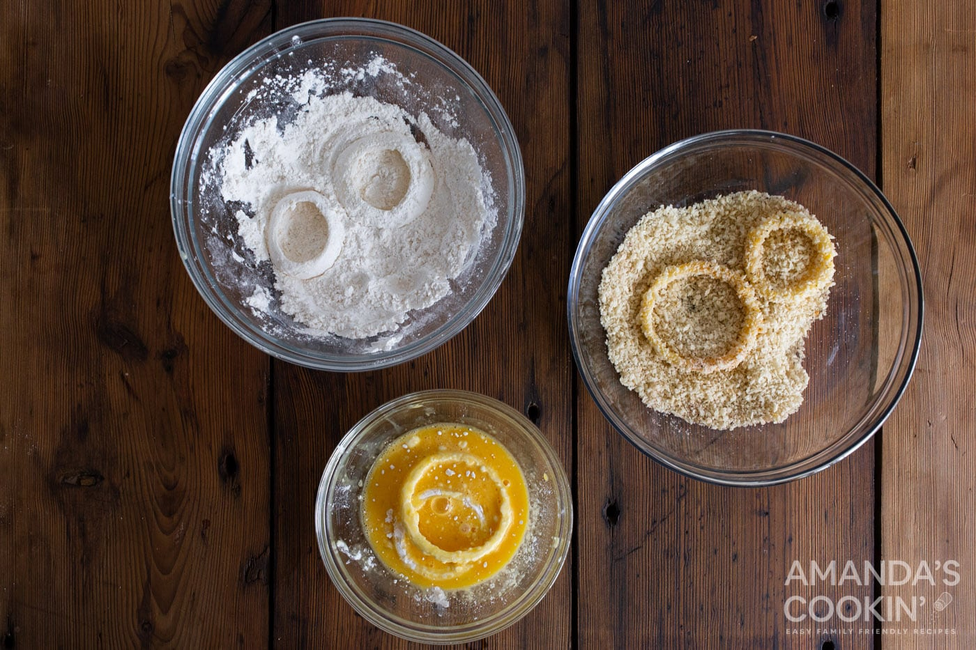 dipping onion in bowl of flour, breadcrumbs, and whisked eggs