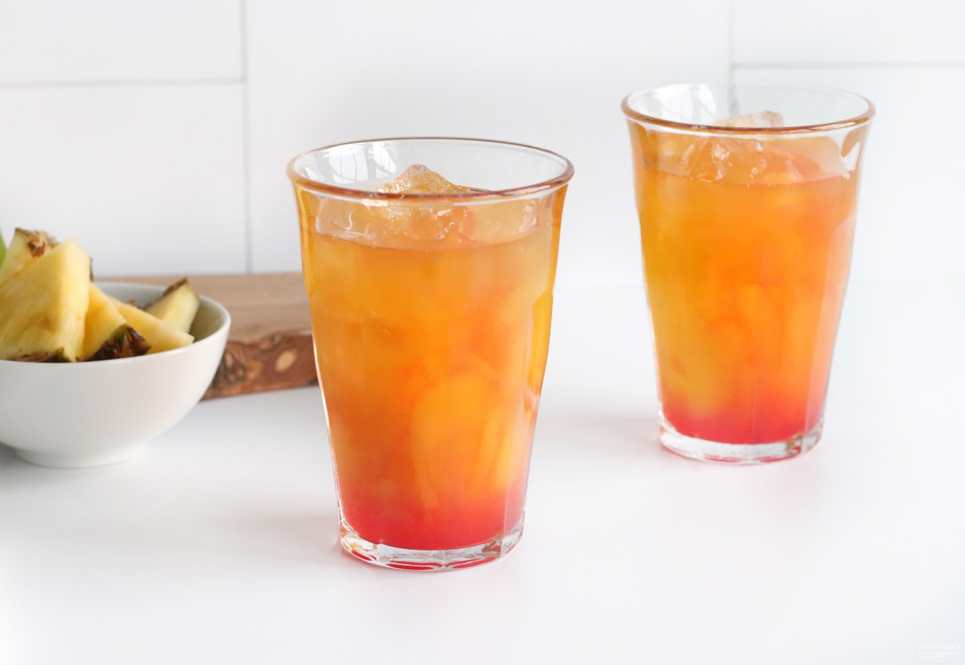 grenadine in a glass of pineapple juice, mango juice, and rum