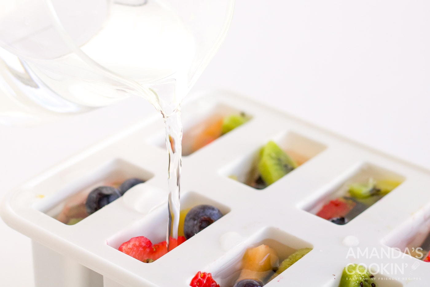 pouring white juice over fruit in popsicle mold