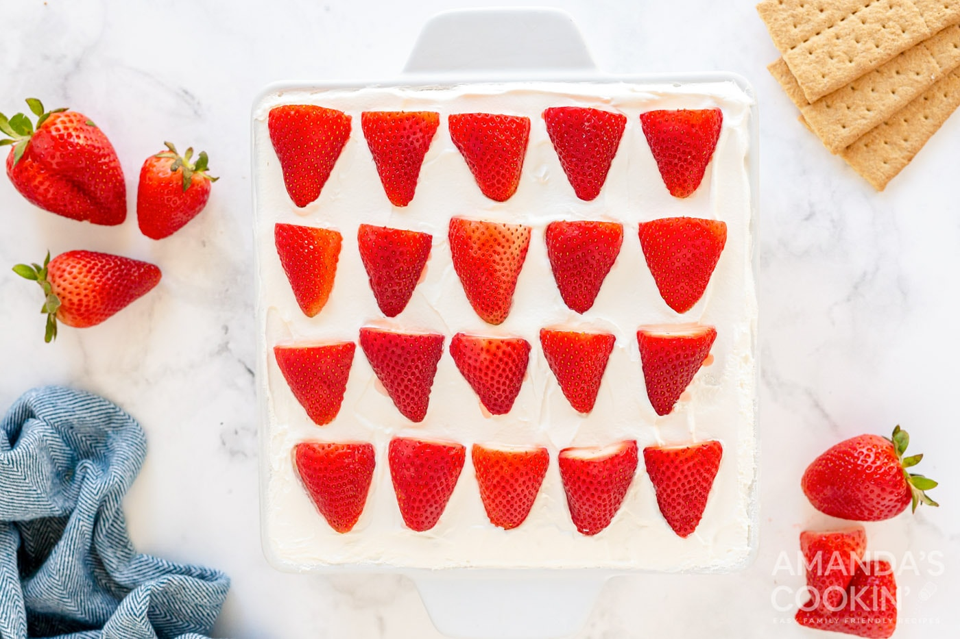 overhead photo of sliced strawberries on top of whipped cream