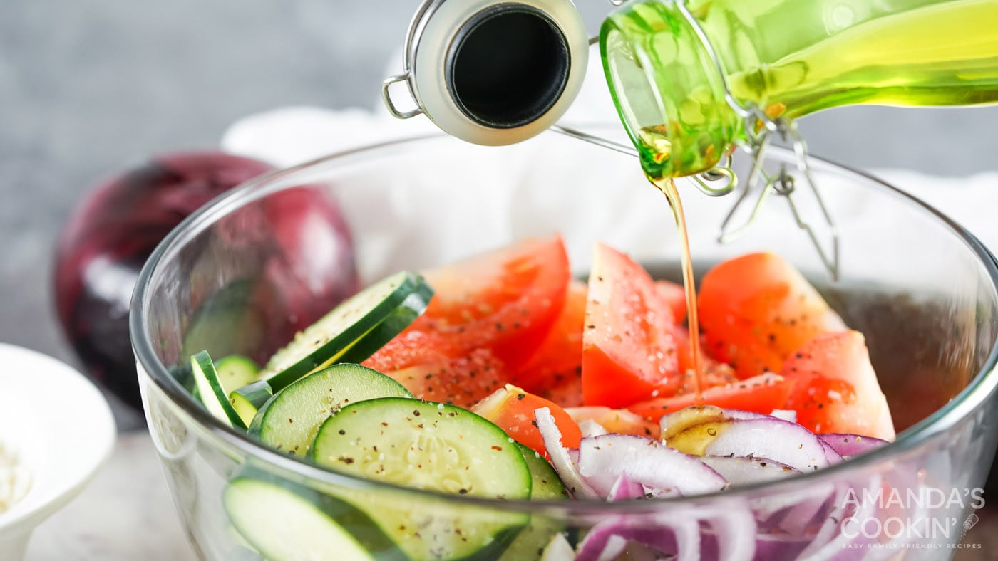 pouring olive oil into cucumber, tomato, and onion salad