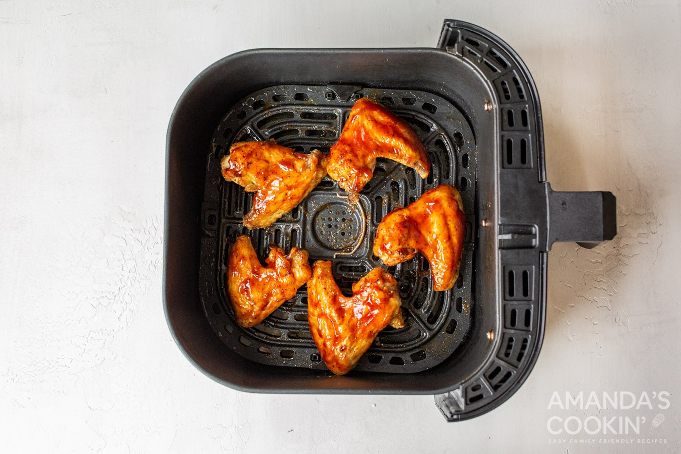 chicken wings in air fryer basket with sauce