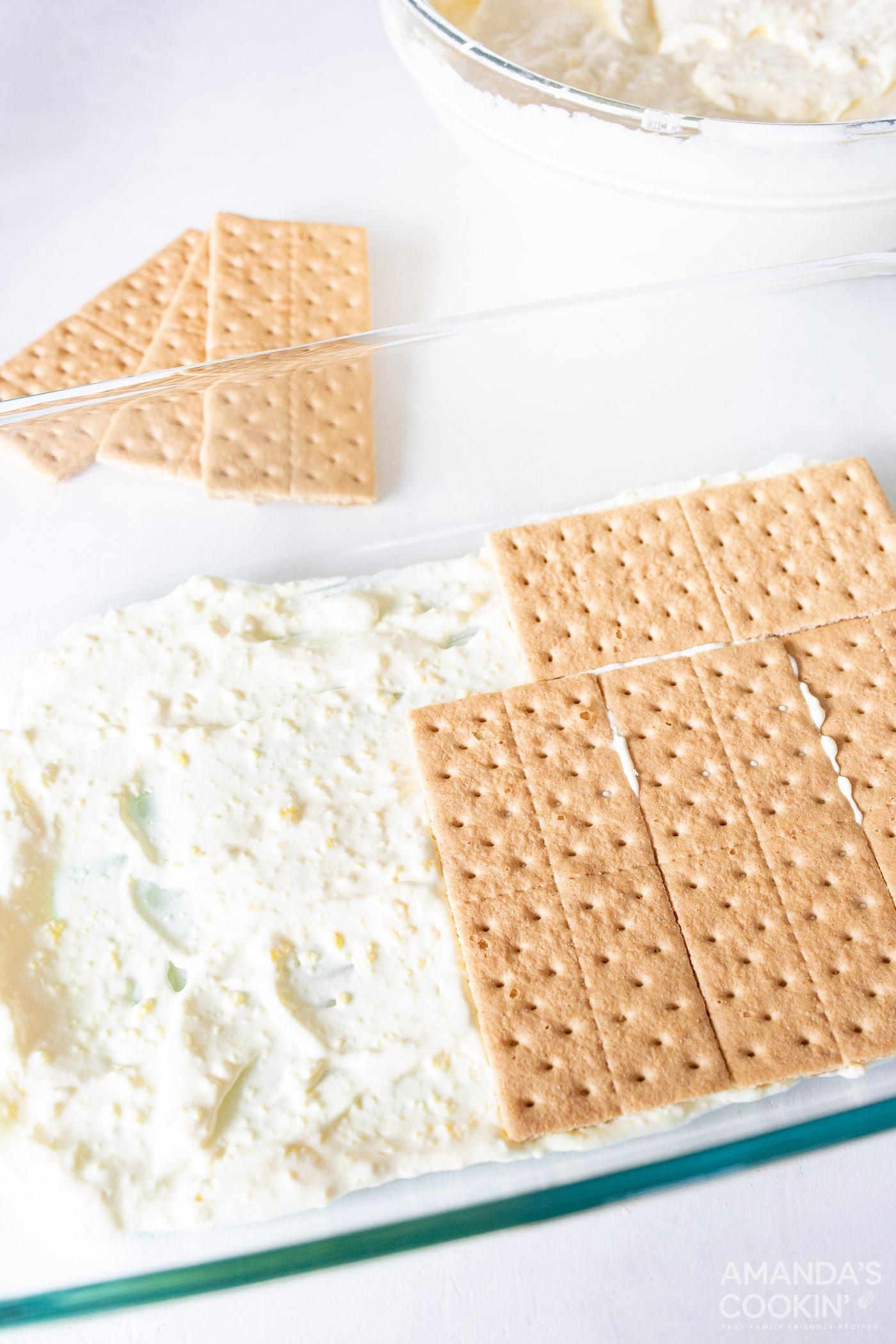 adding graham crackers to 13x9 baking dish with lemon pudding mix