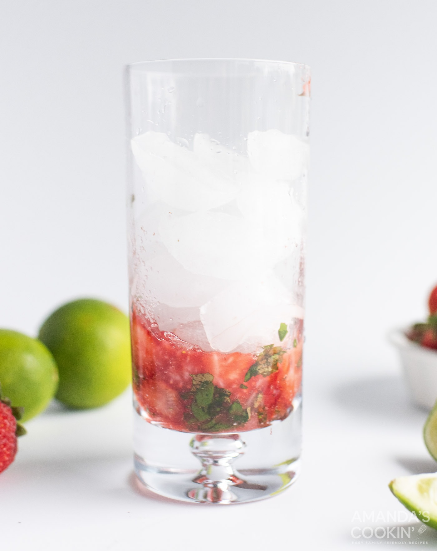muddled strawberries and mint in a glass with ice