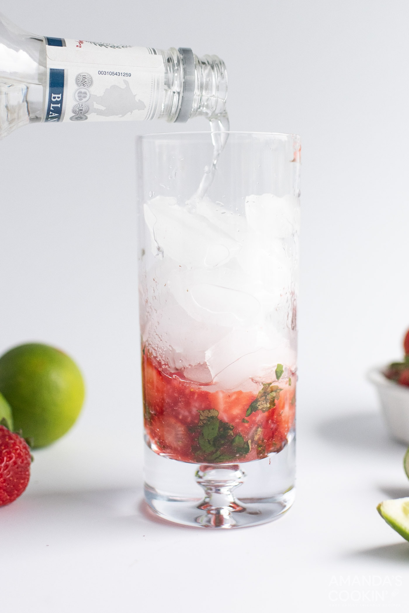 pouring club soda into highball glass with strawberries and mint