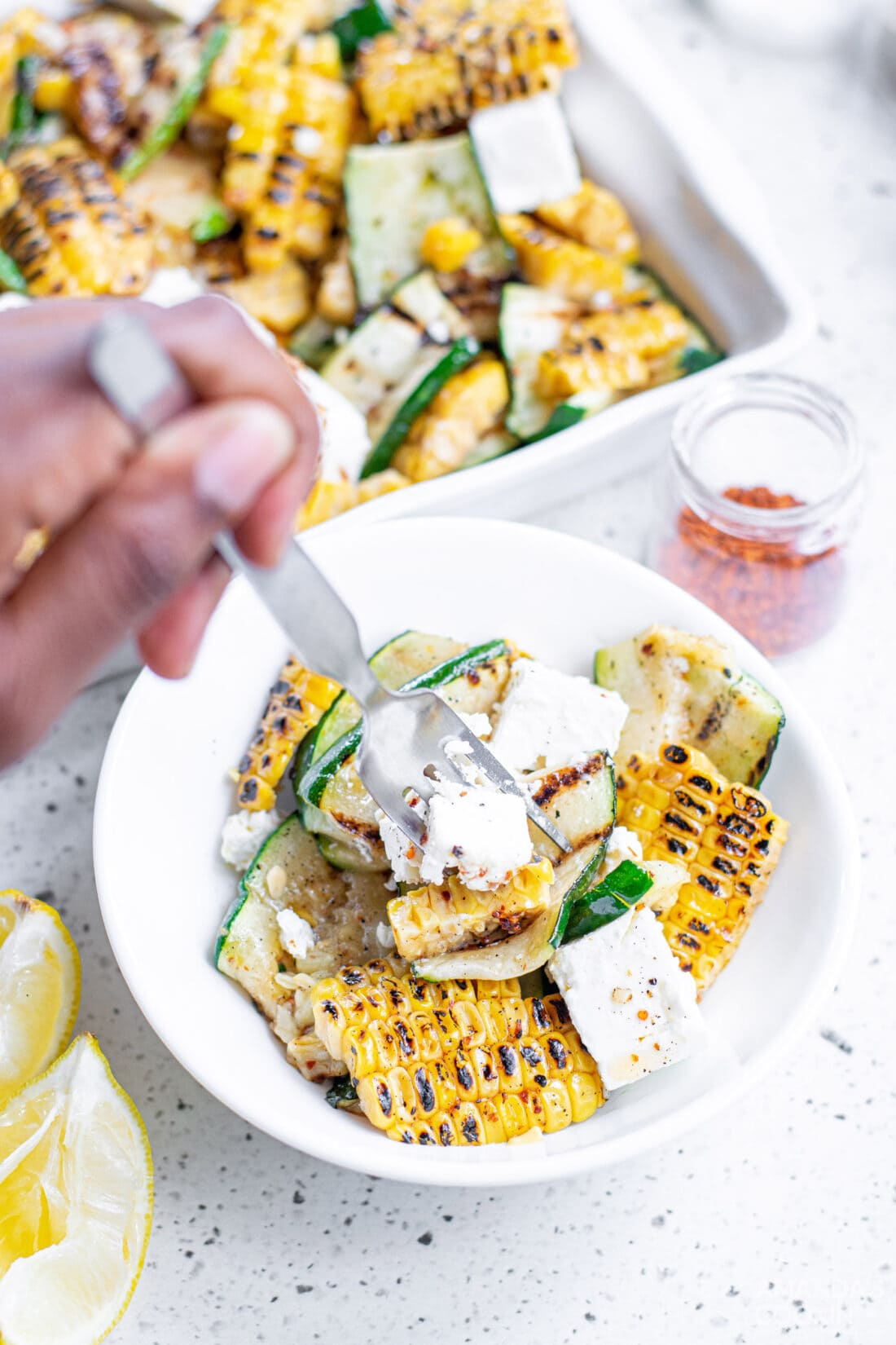 grabbing some Grilled Corn & Zucchini Salad with Feta with a fork