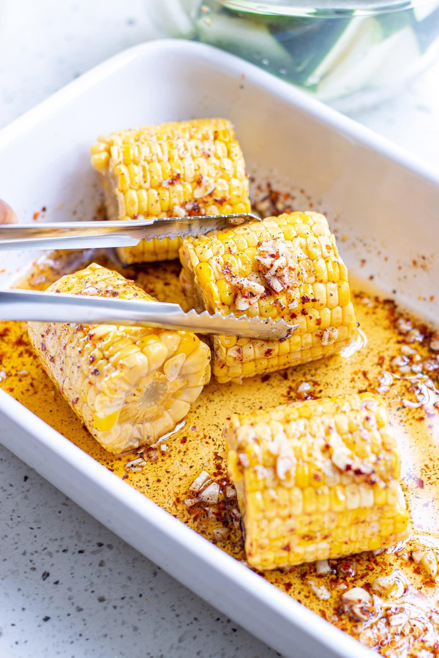 tongs holding marinated corn on the cob