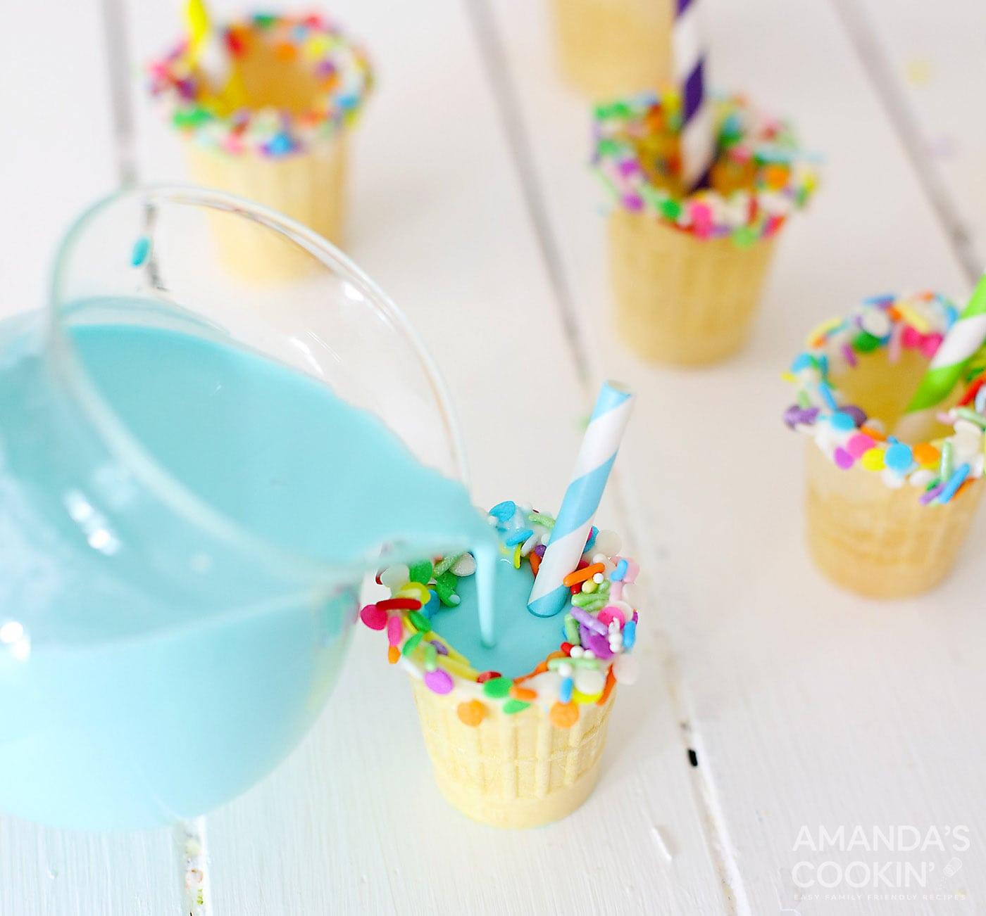 pouring blue rum chata into ice cream cone shot glasses