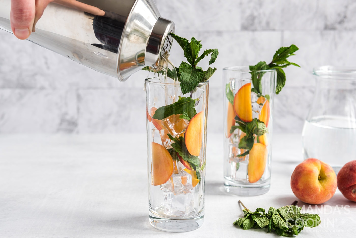 cocktail shaker pouring peach mojito into glass with peaches and mint