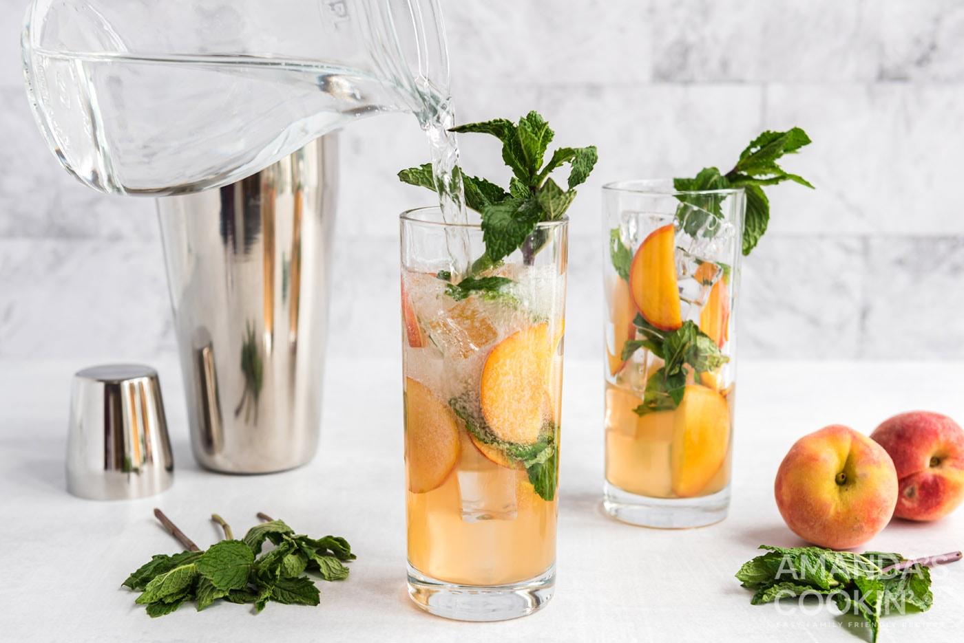 adding club soda to peach mojito in glass