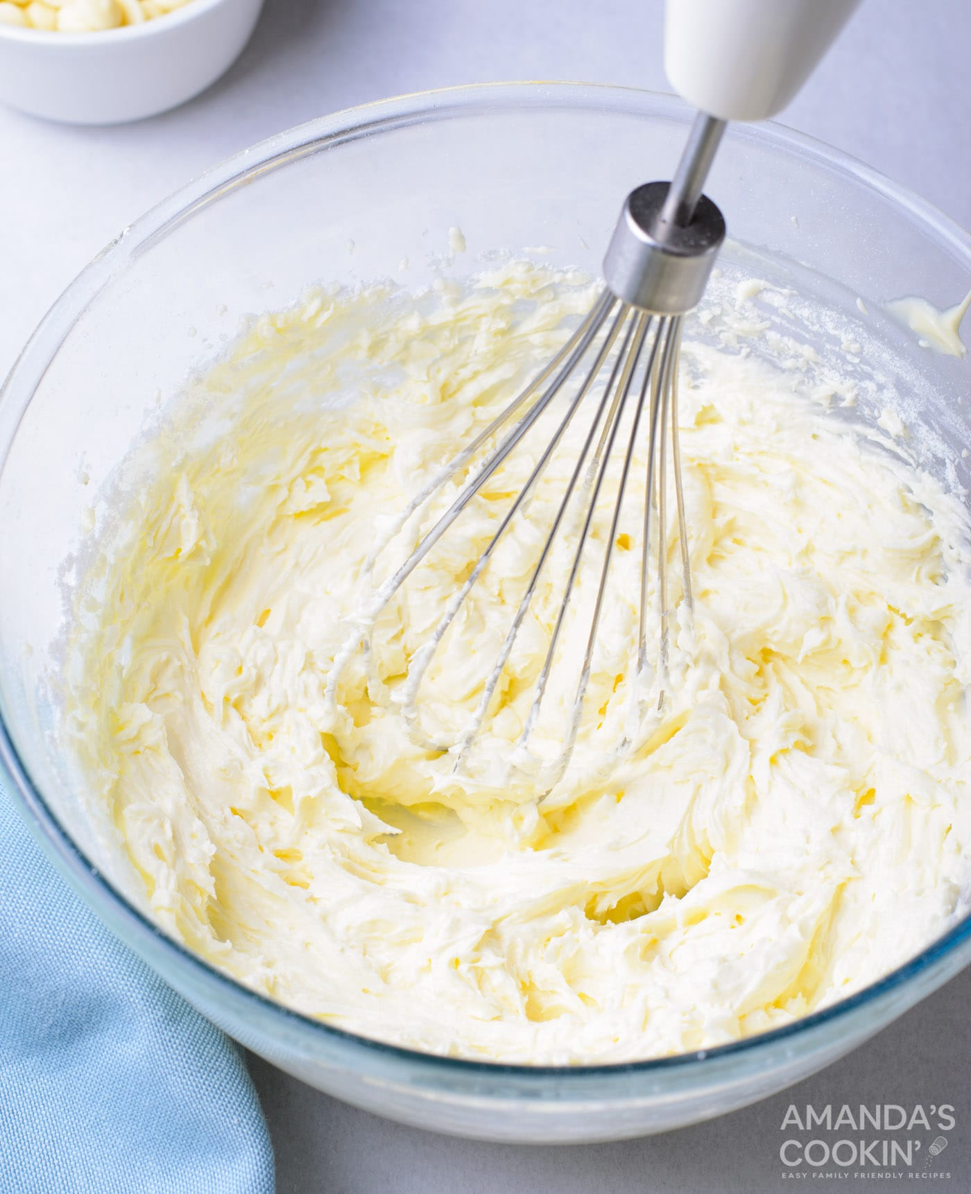 mixing buttercream frosting in a bowl
