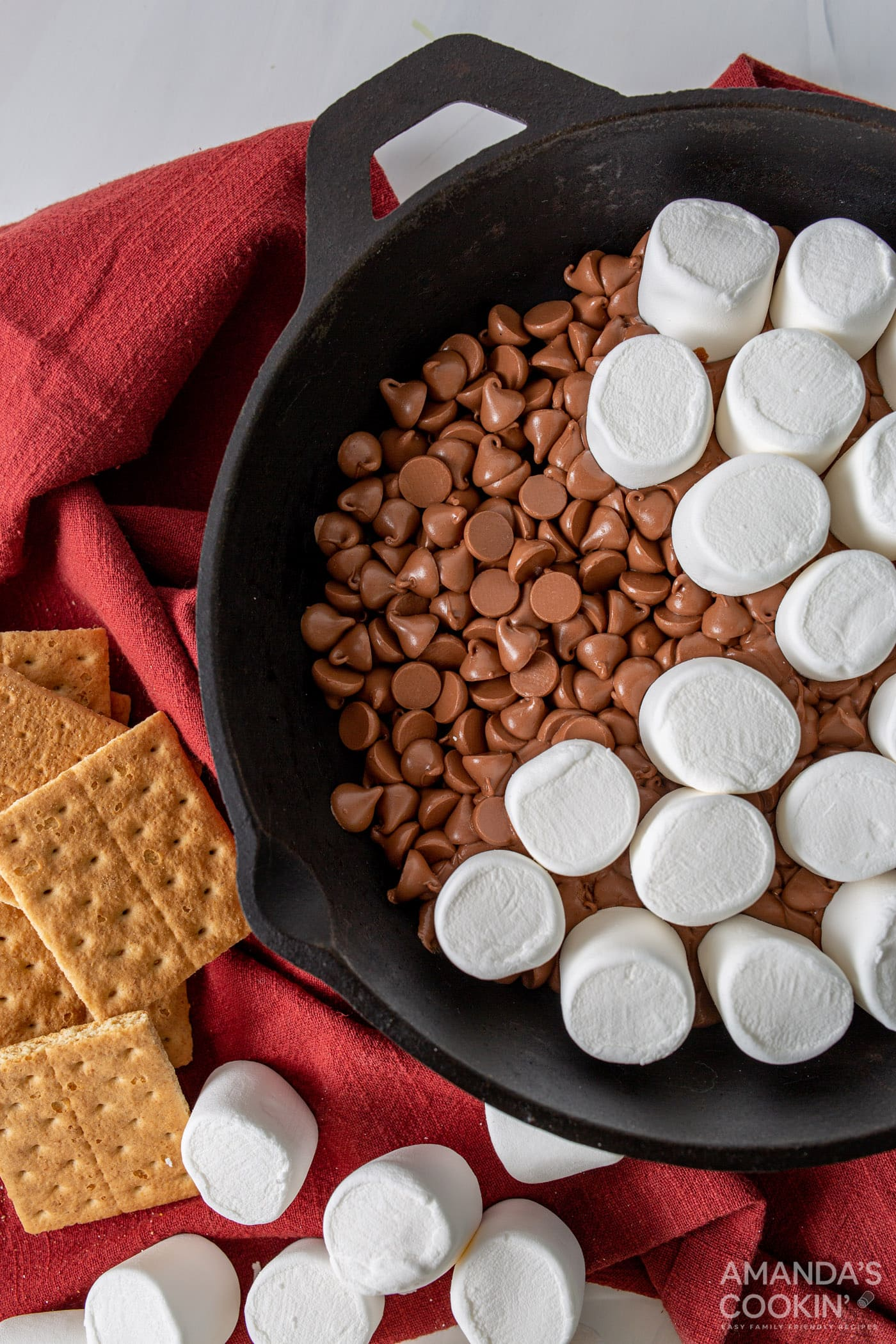 marshmallows on top of chocolate chips in a skillet