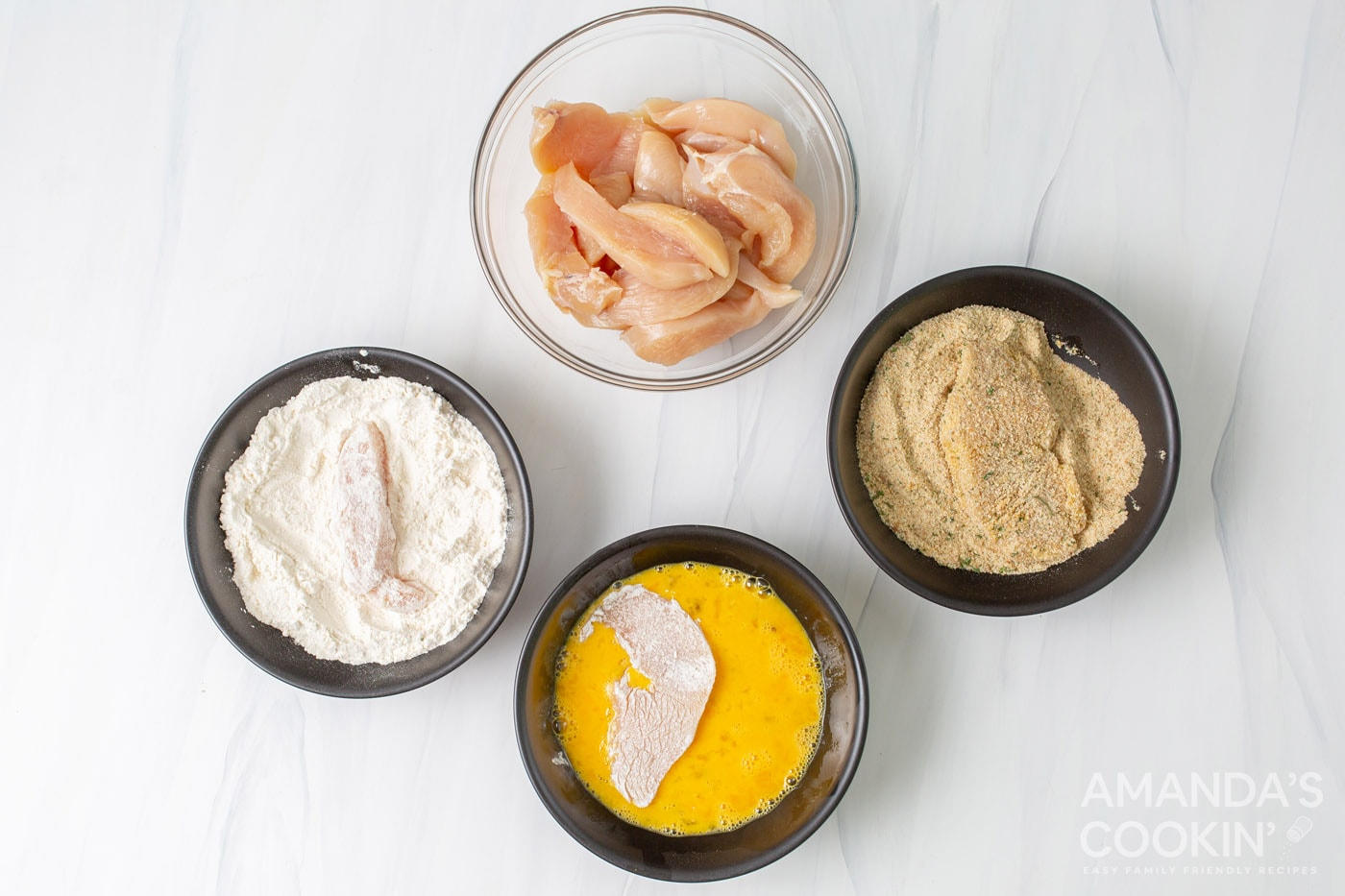 flour, eggs,, breadcrumbs, and chicken in bowls