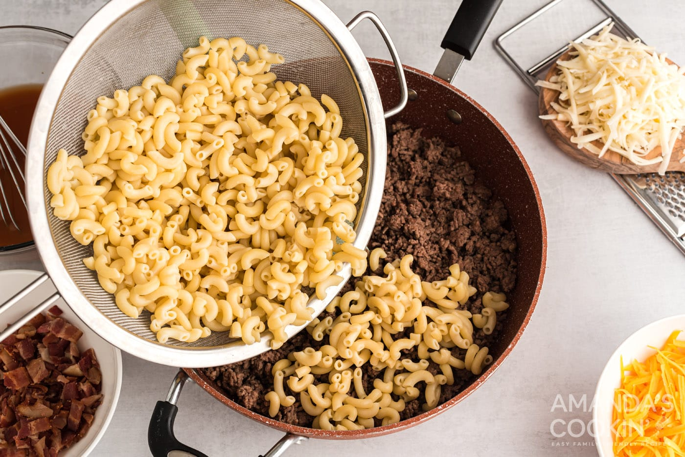 pouring drained pasta over beef mixture in skillet