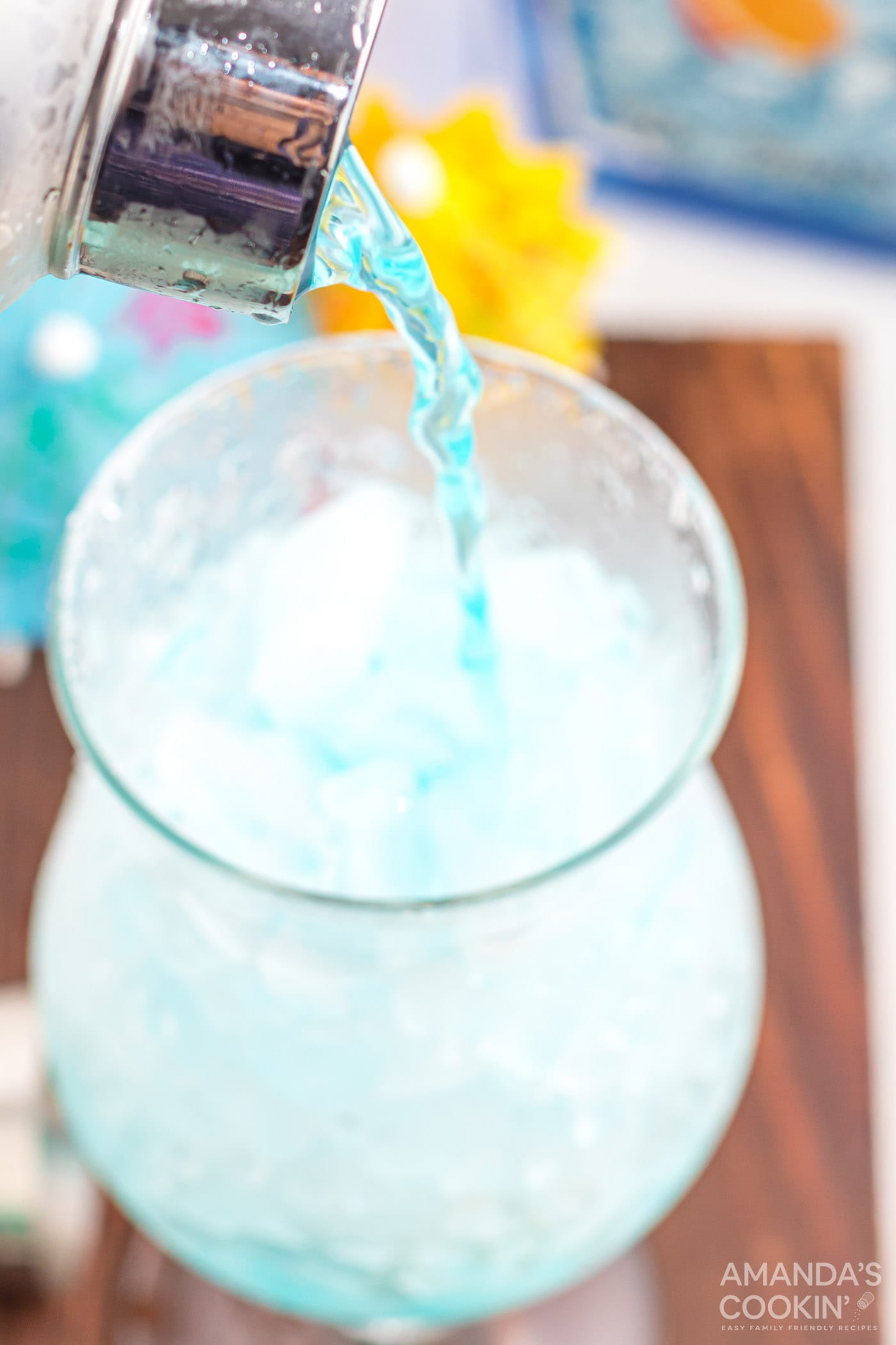 pouring blue lagoon cocktail into a hurricane glass
