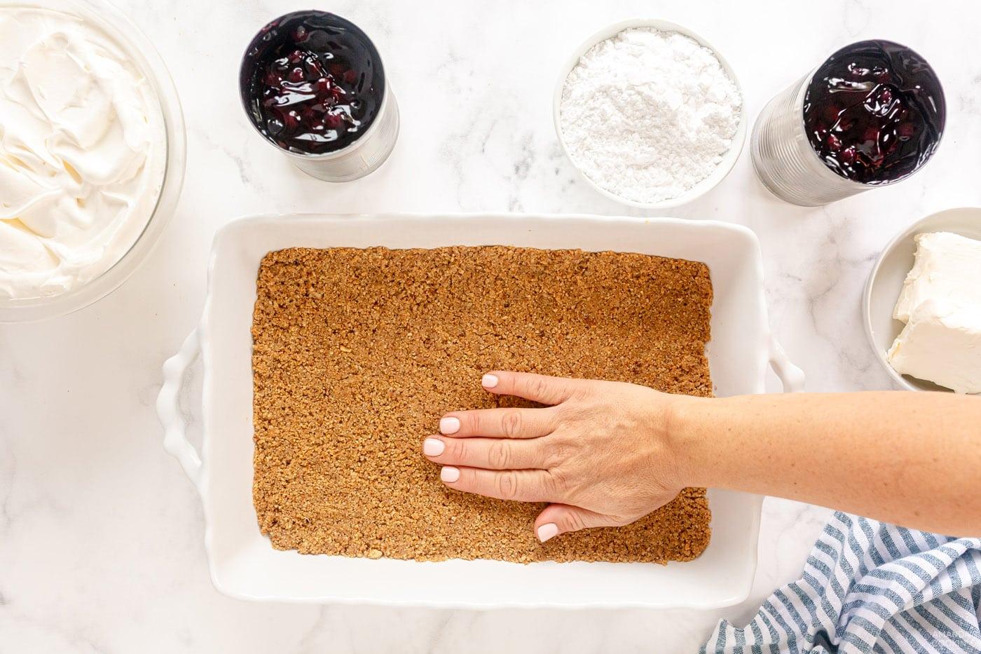 pressing graham cracker crust into pan