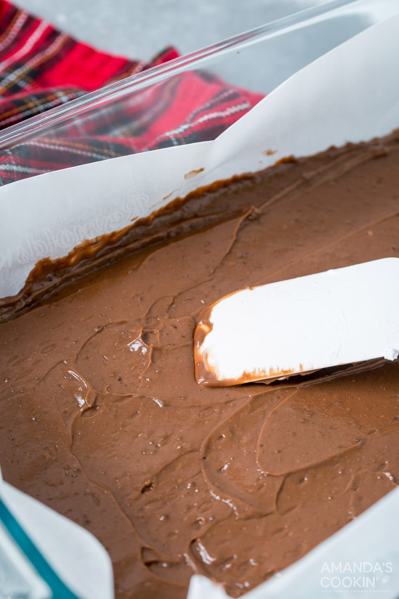 rubber spatula smoothing chocolate pudding into pan