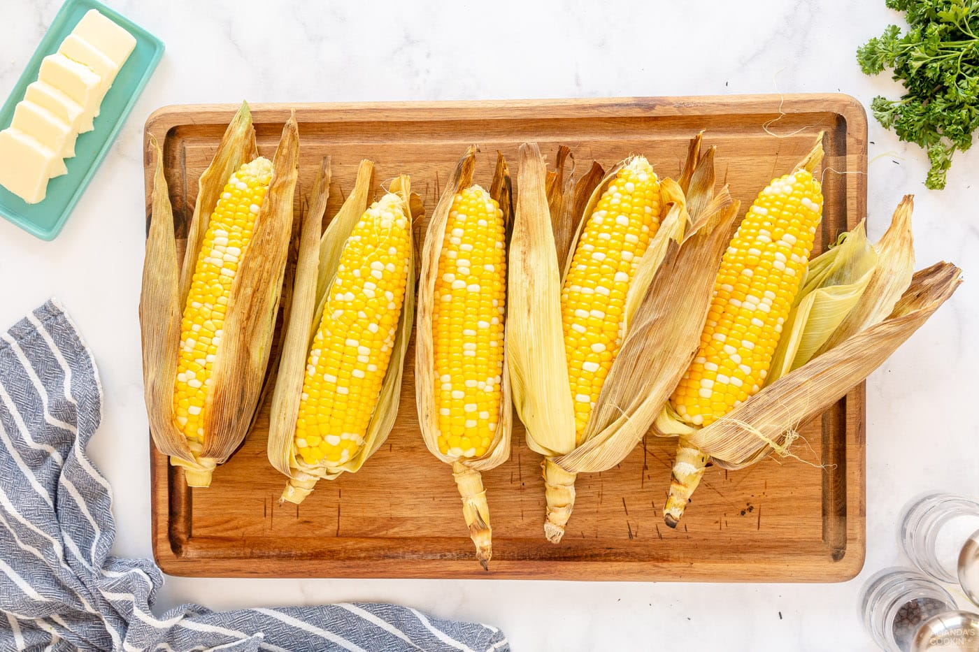 peeled corn on the cob on a cutting board