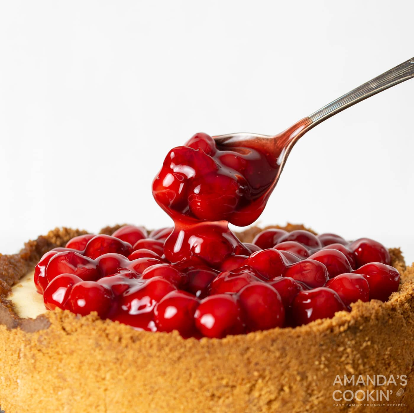 spoon with cherry pie filling on cheesecake