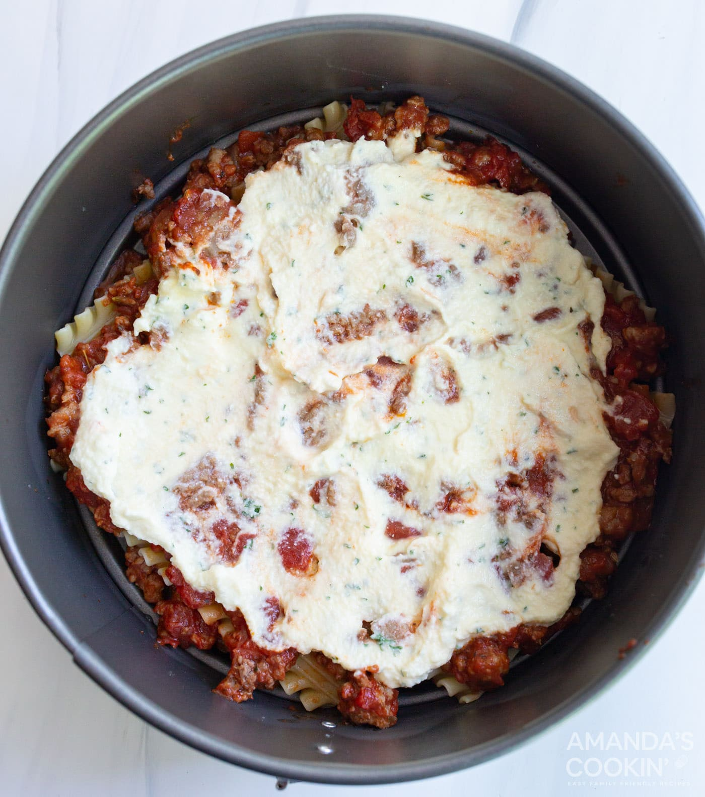 ricotta mixture on top of lasagna noodles in a pan