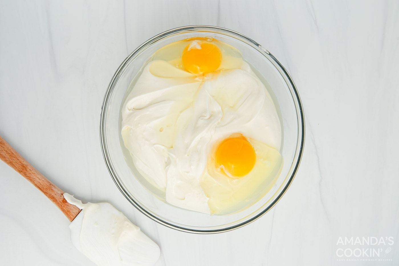 eggs in a mixing bowl with cream cheese and sour cream mixture