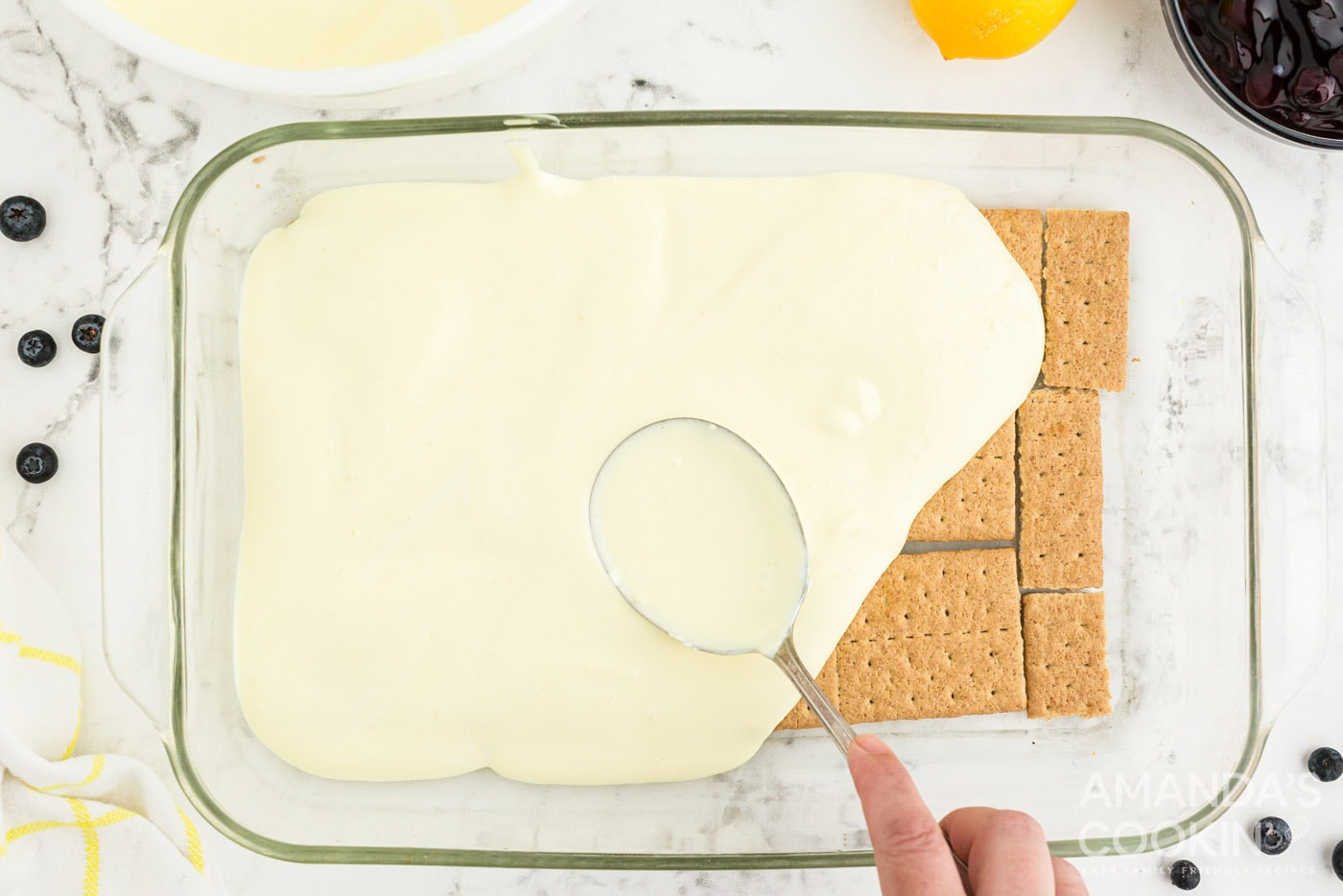 spooning pudding layer over graham crackers in casserole dish