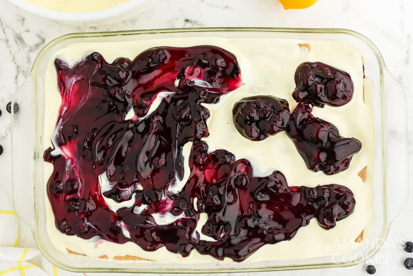 blueberry pie filling on top of pudding in a casserole dish