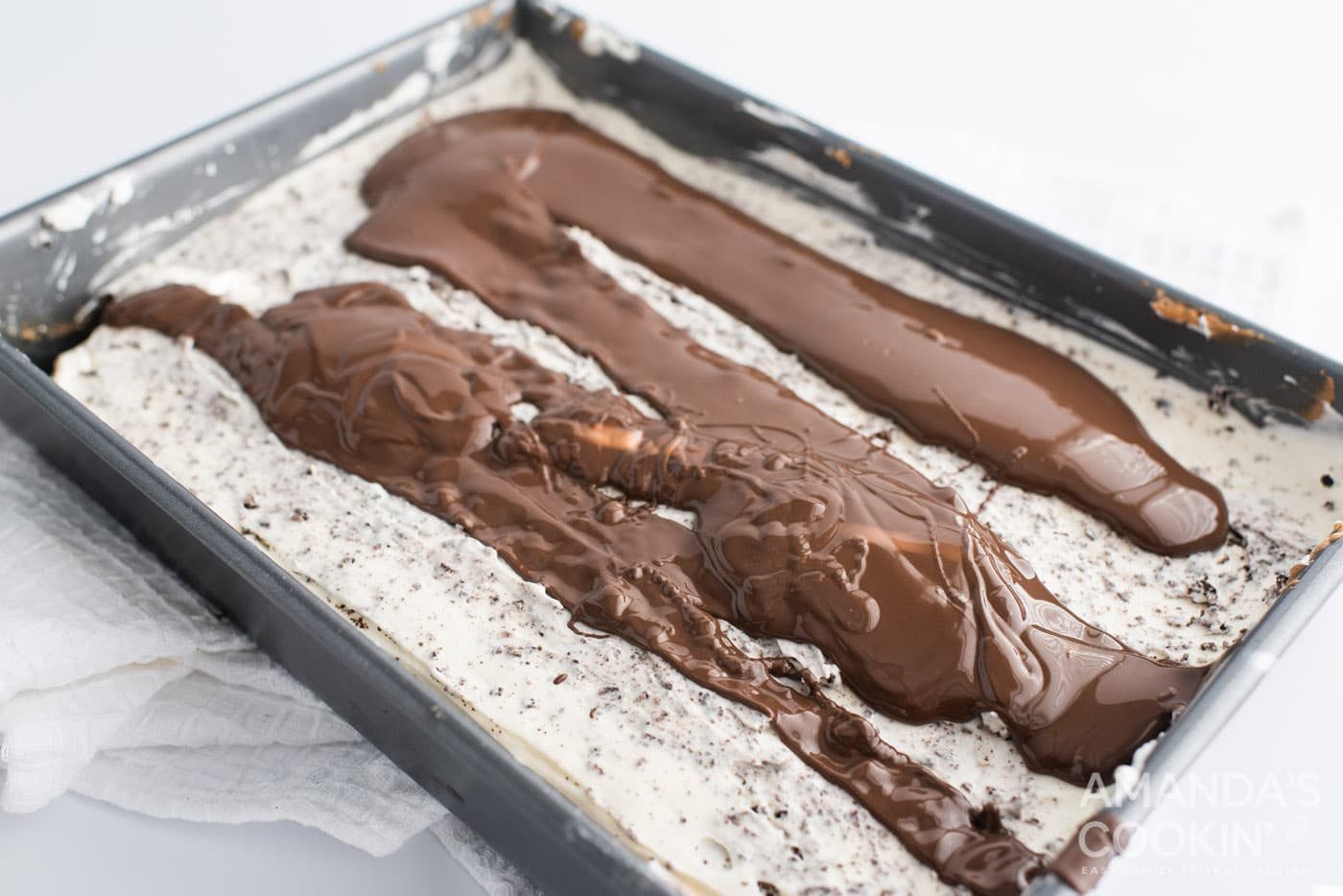 chocolate ganache topping on oreo cheesecake in a pan