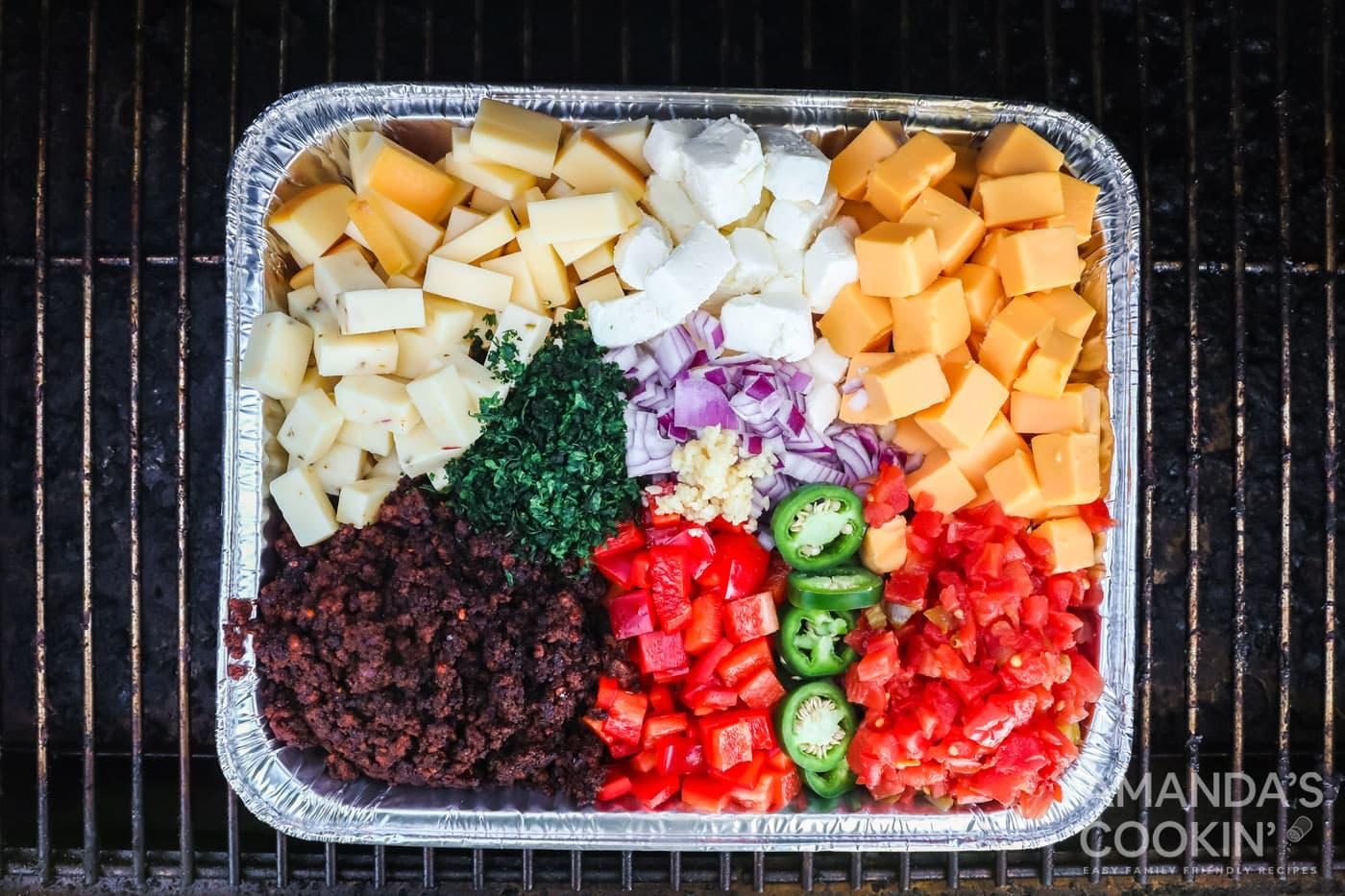 queso dip ingredients in a 13x9 foil pan