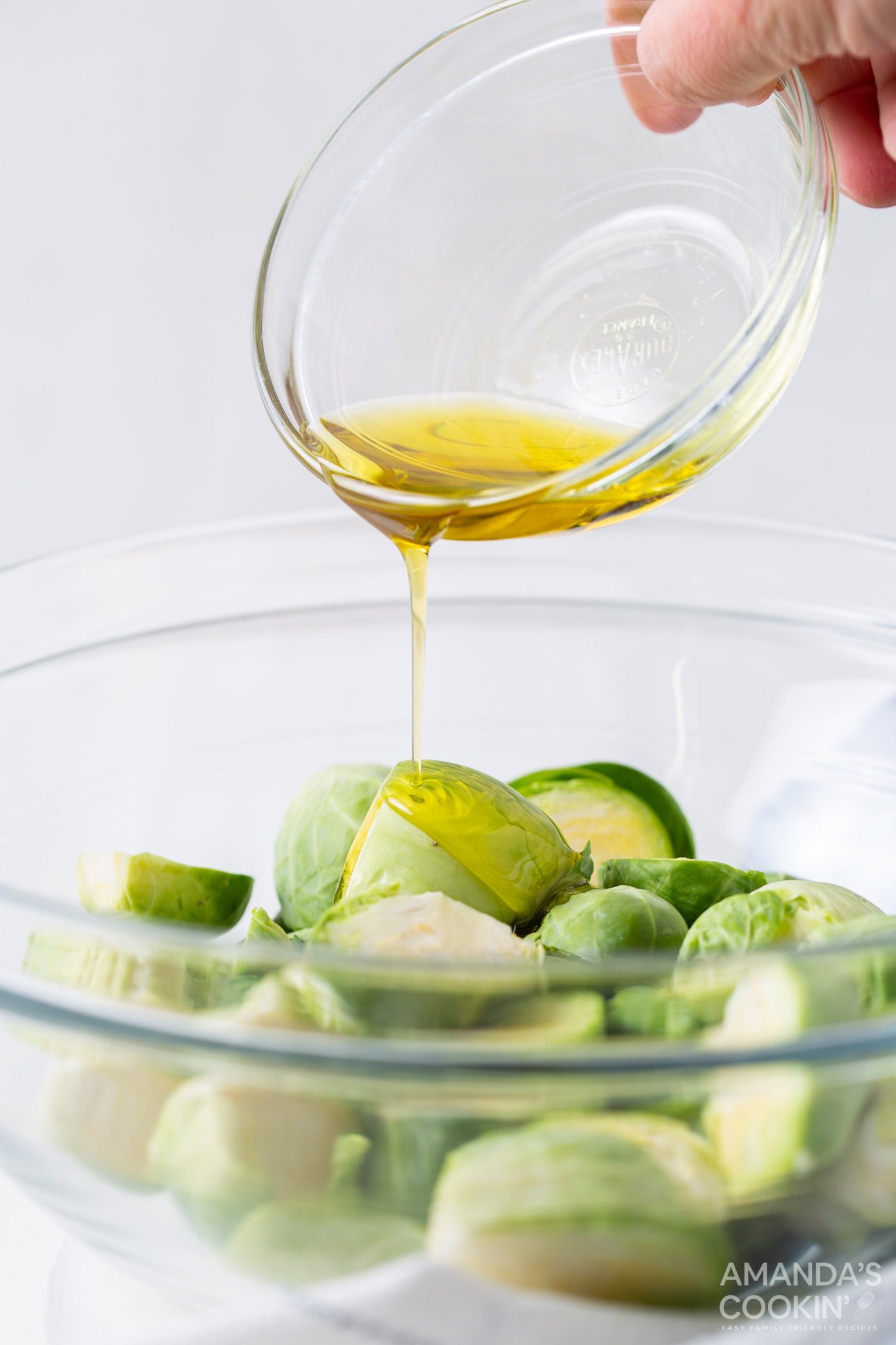 pouring olive oil onto brussels sprouts