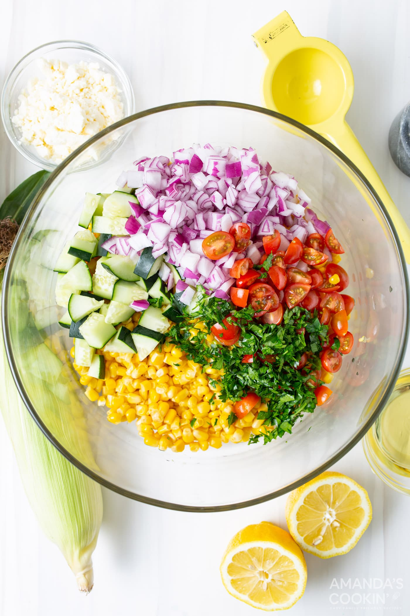 mixing bowl with corn, tomatoes, basil, cucumber, and red onion