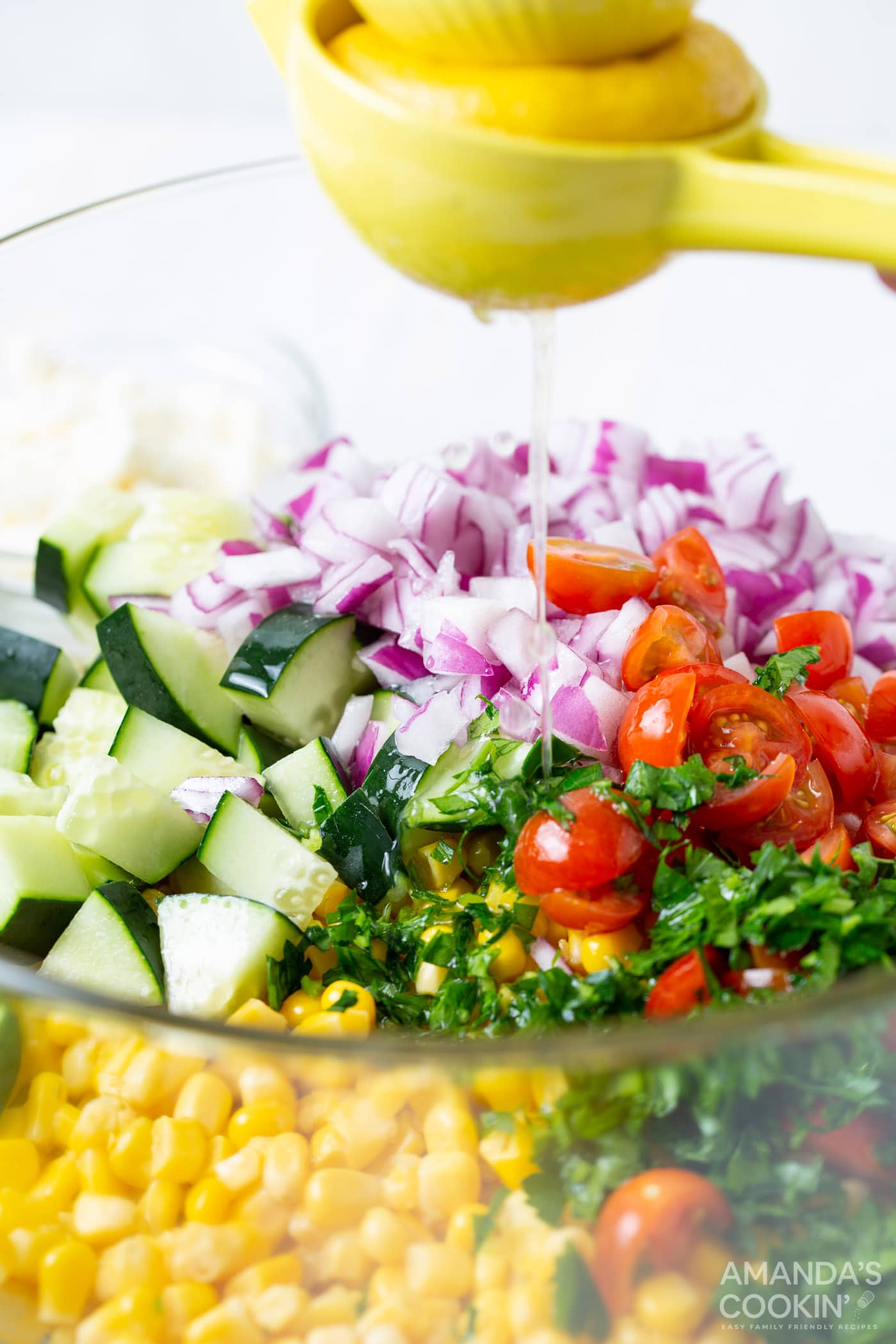 squeezing lemon juice onto corn salad