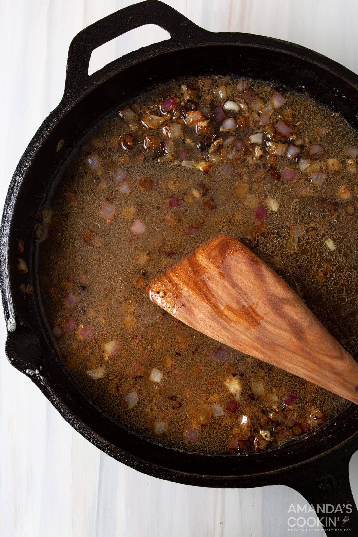 wood spatula stirring in garlic on a skillet