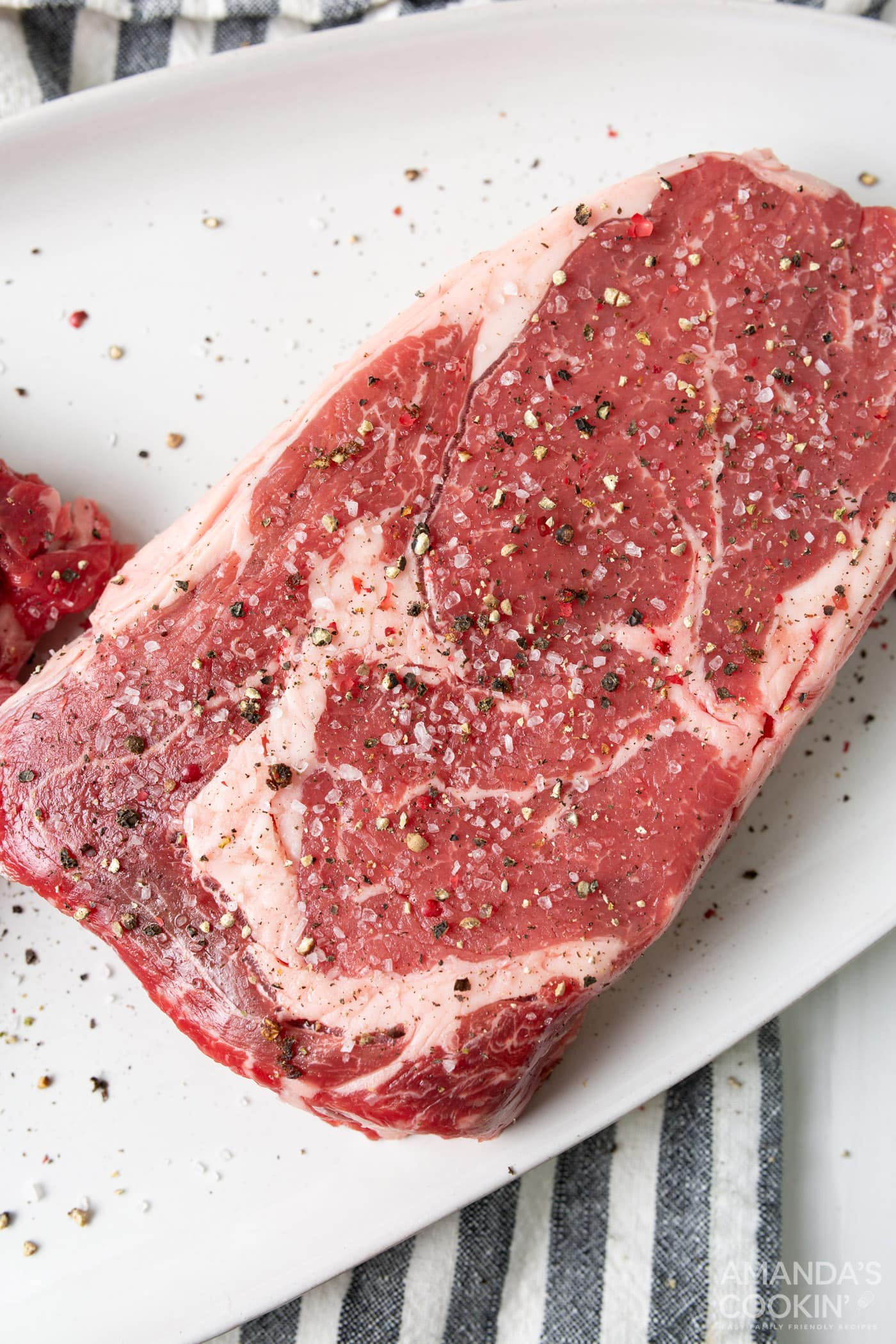 new york strip steak on a plate with salt and pepper