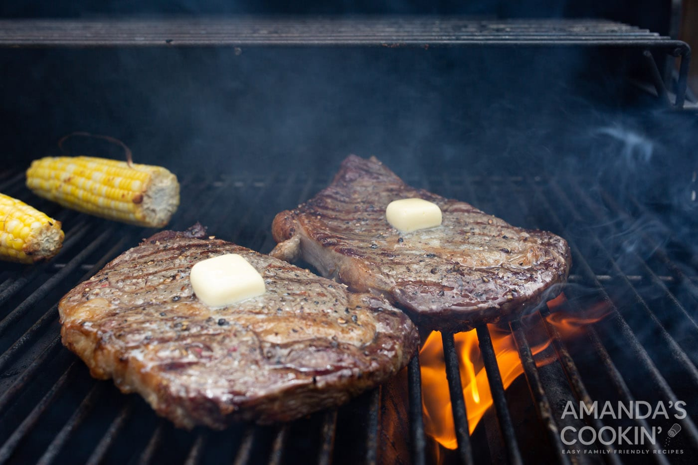 pats of butter on grilled new york strips steaks