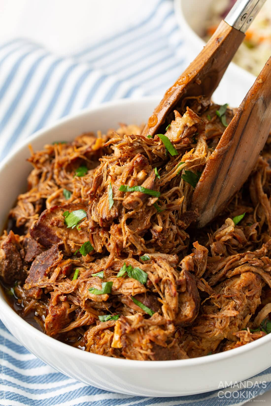 tongs in a bowl of Instant Pot Pulled Pork