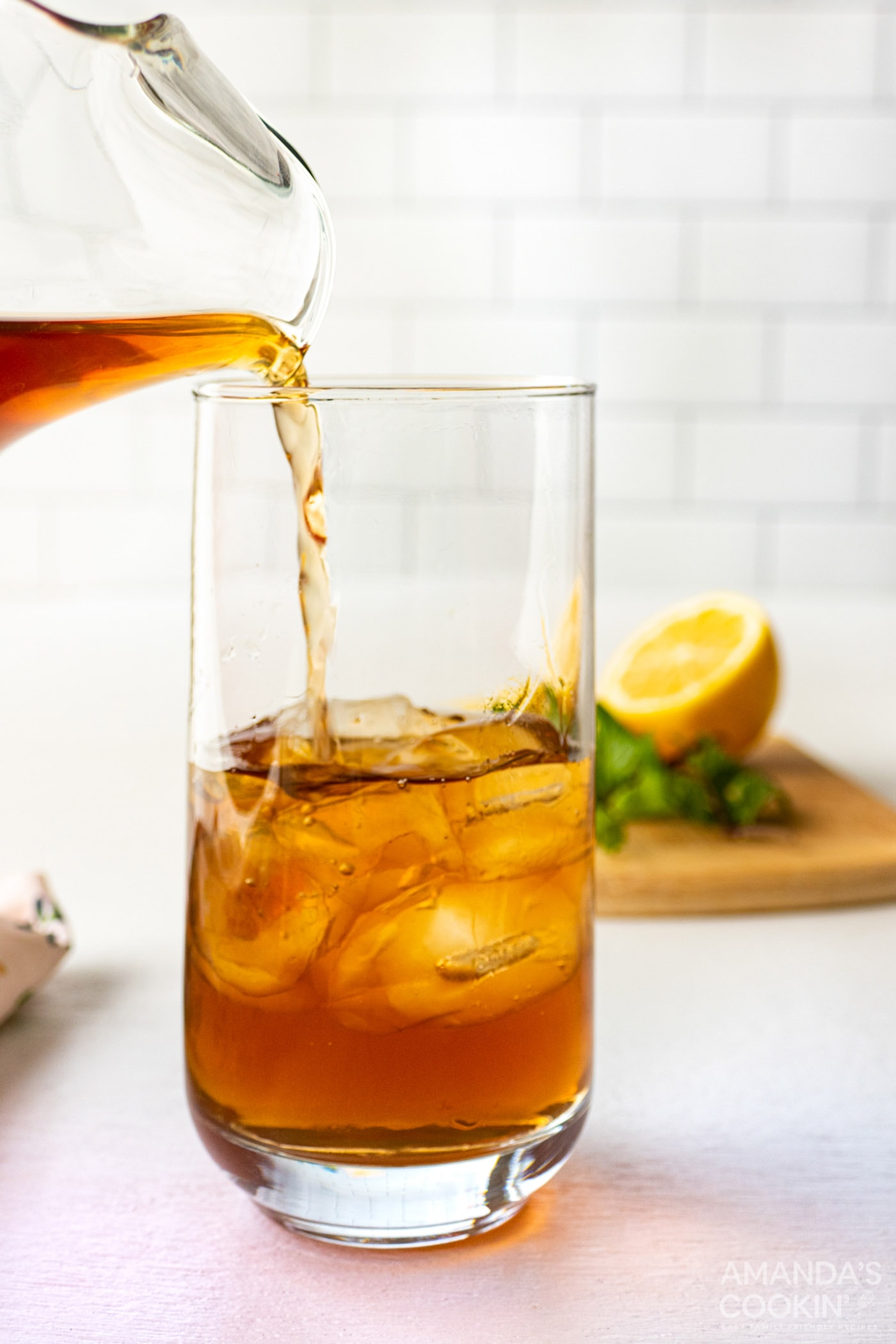 pitcher pouring iced tea into tall glass with ice