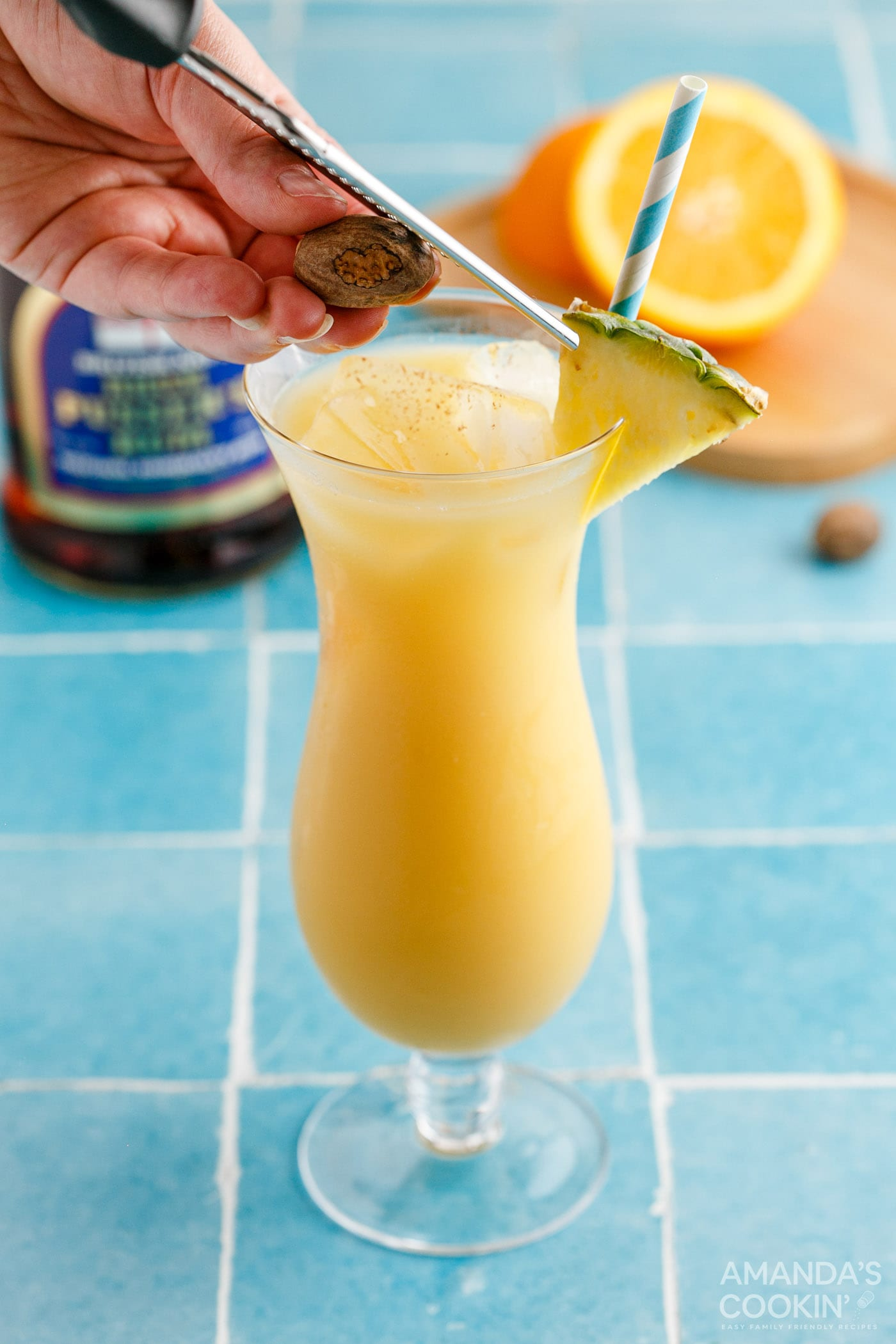 adding pineapple wedge garnish to painkiller cocktail